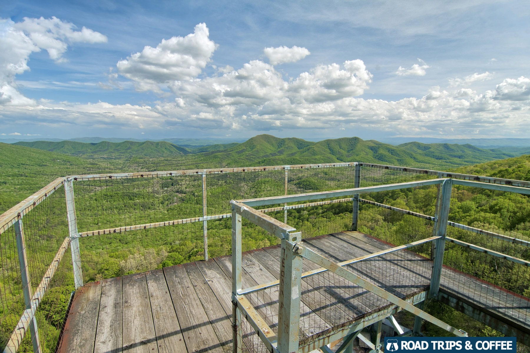A wooden platform at the top of the steel frame Big Walker Lookout with a view of partly cloudy skies over a lush green mountain landscape in Wytheville, Virginia