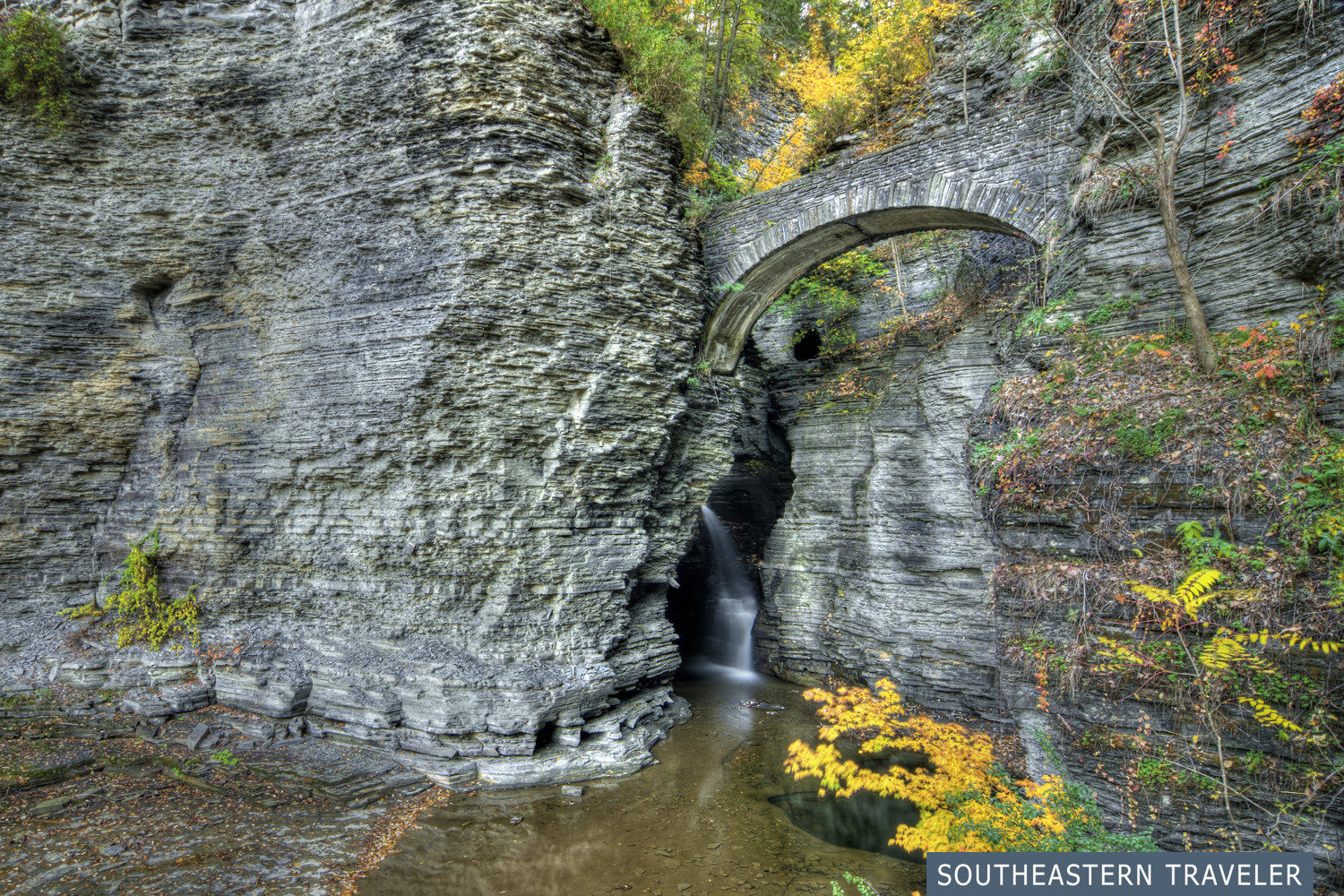 A stone bridge crossing a waterfall at the entrance to the Gorge Trail at Watkins Glen State Park in New York