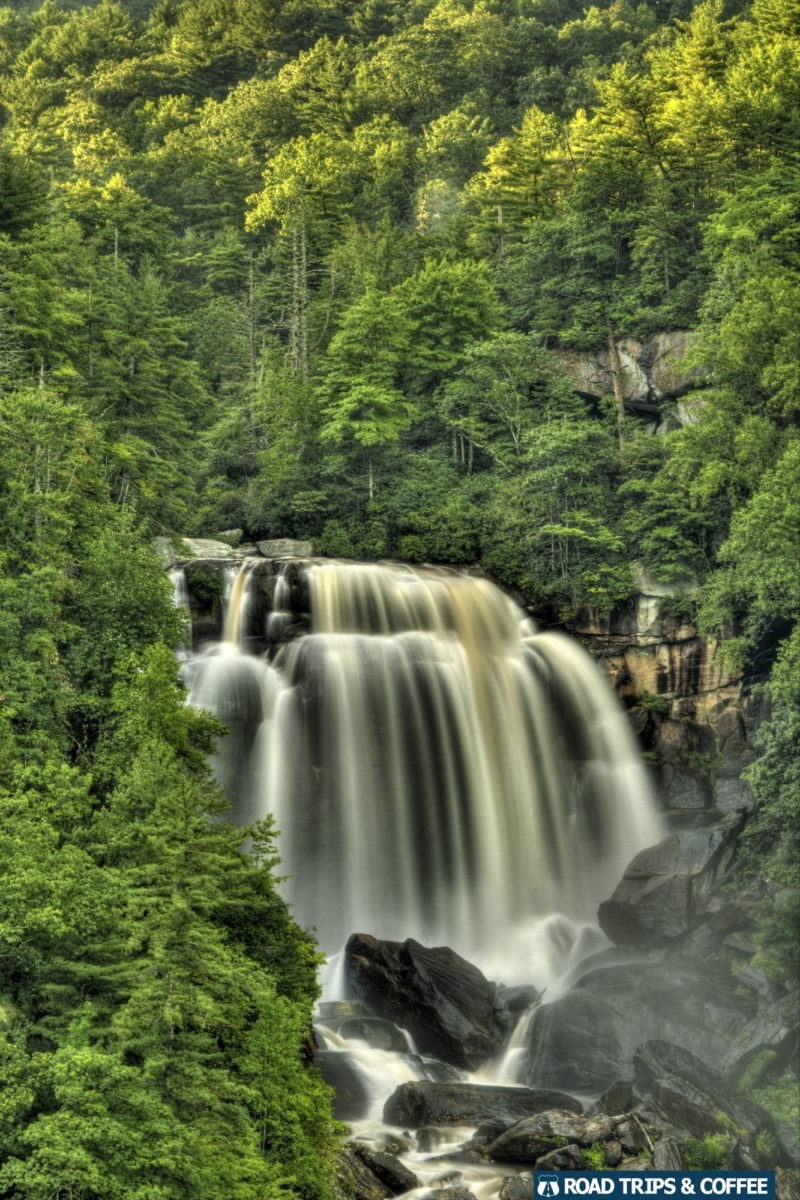 A tremendous amount of water spills over a waterfall surrounded by lush green trees at Upper Whitewater Falls in South Carolina.