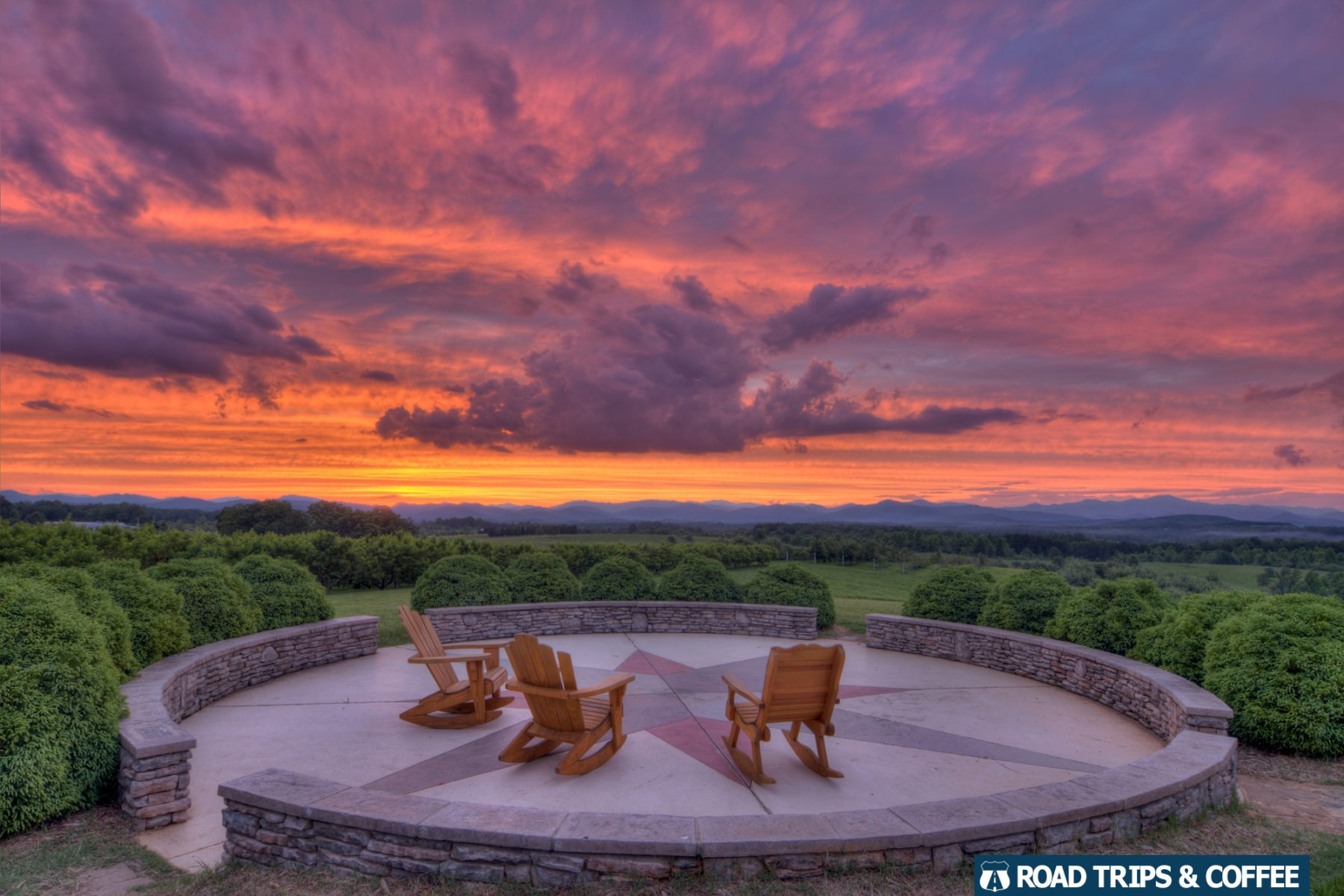 A brilliant orange sunset colors the sky over a trio of wooden rocking chairs on a circular stone patio at Chattooga Belle Farm in South Carolina.