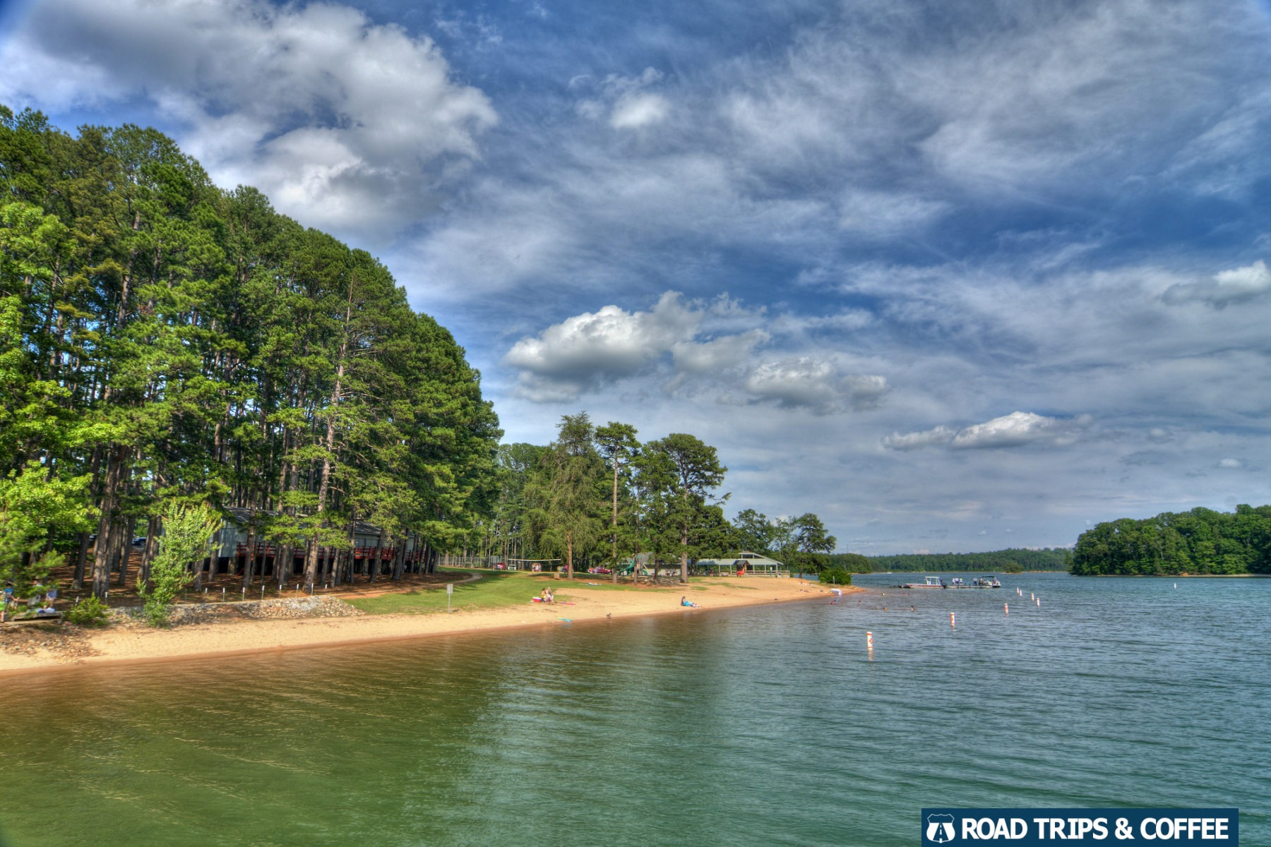 A long sandy beach surrounded by towering green trees and calm water at a county park in South Carolina.