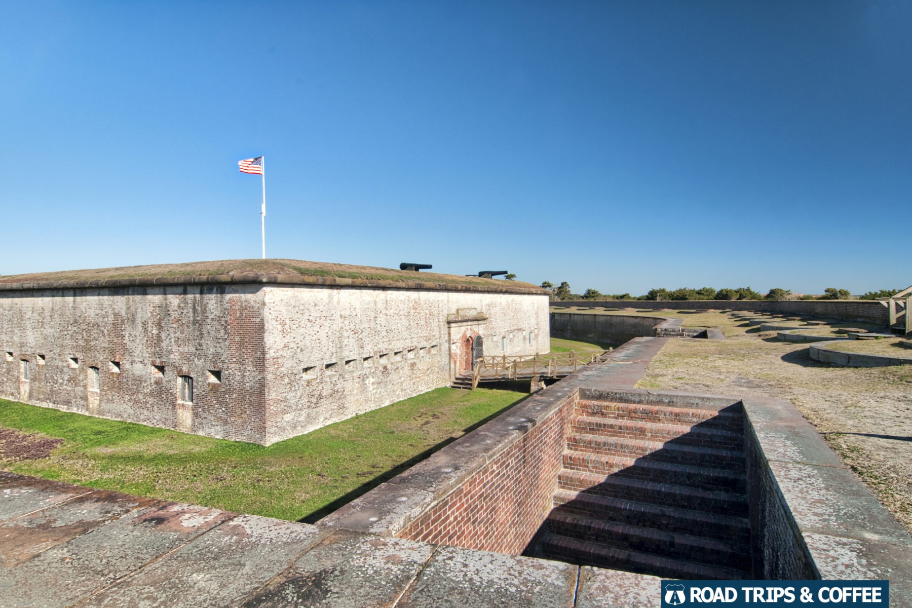 A brick staircase leads down into an underground room along the outer wall at Fort Macon State Park in Atlantic Beach, North Carolina