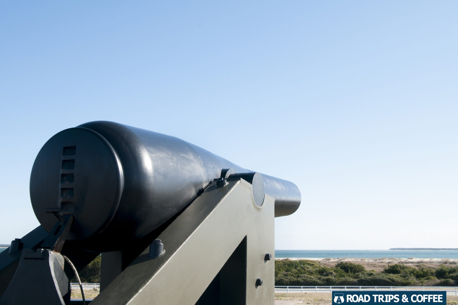 A large canon overlooking the distant Atlantic Ocean from the top of Fort Macon State Park in Atlantic Beach, North Carolina