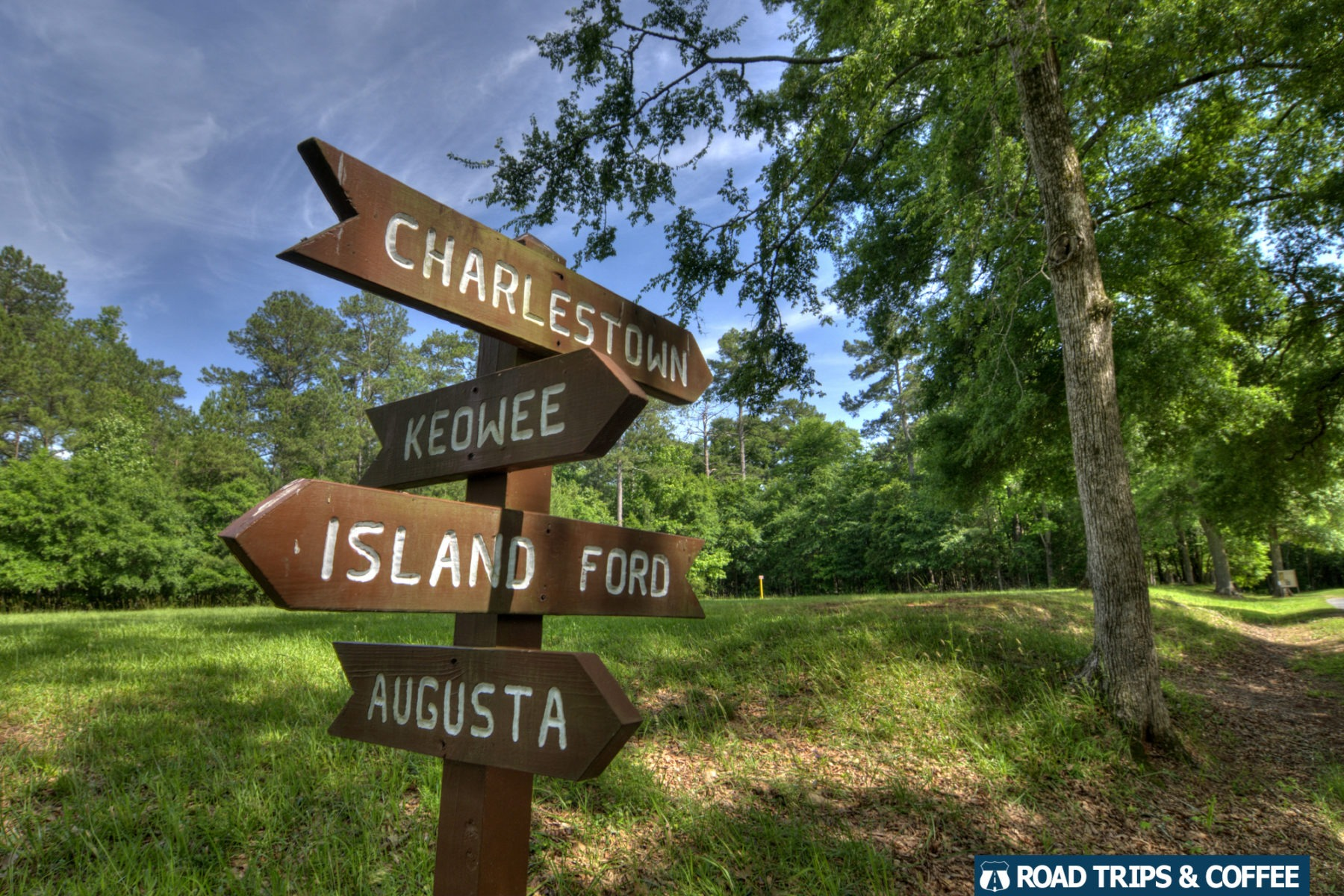 A rustic sign pointing to various cities around of Ninety Six National Historic Site in Ninety Six, South Carolina