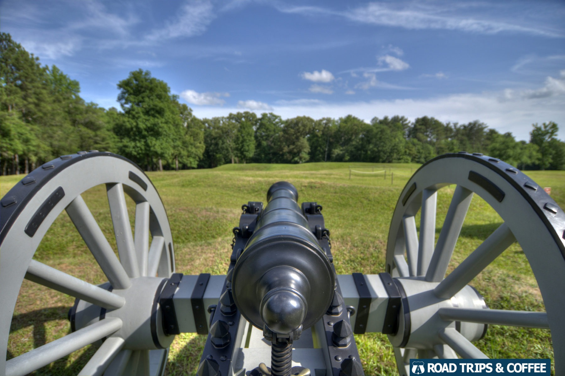 A canon overlooking a large field along the hiking trail at Ninety Six National Historic Site in Ninety Six, South Carolina