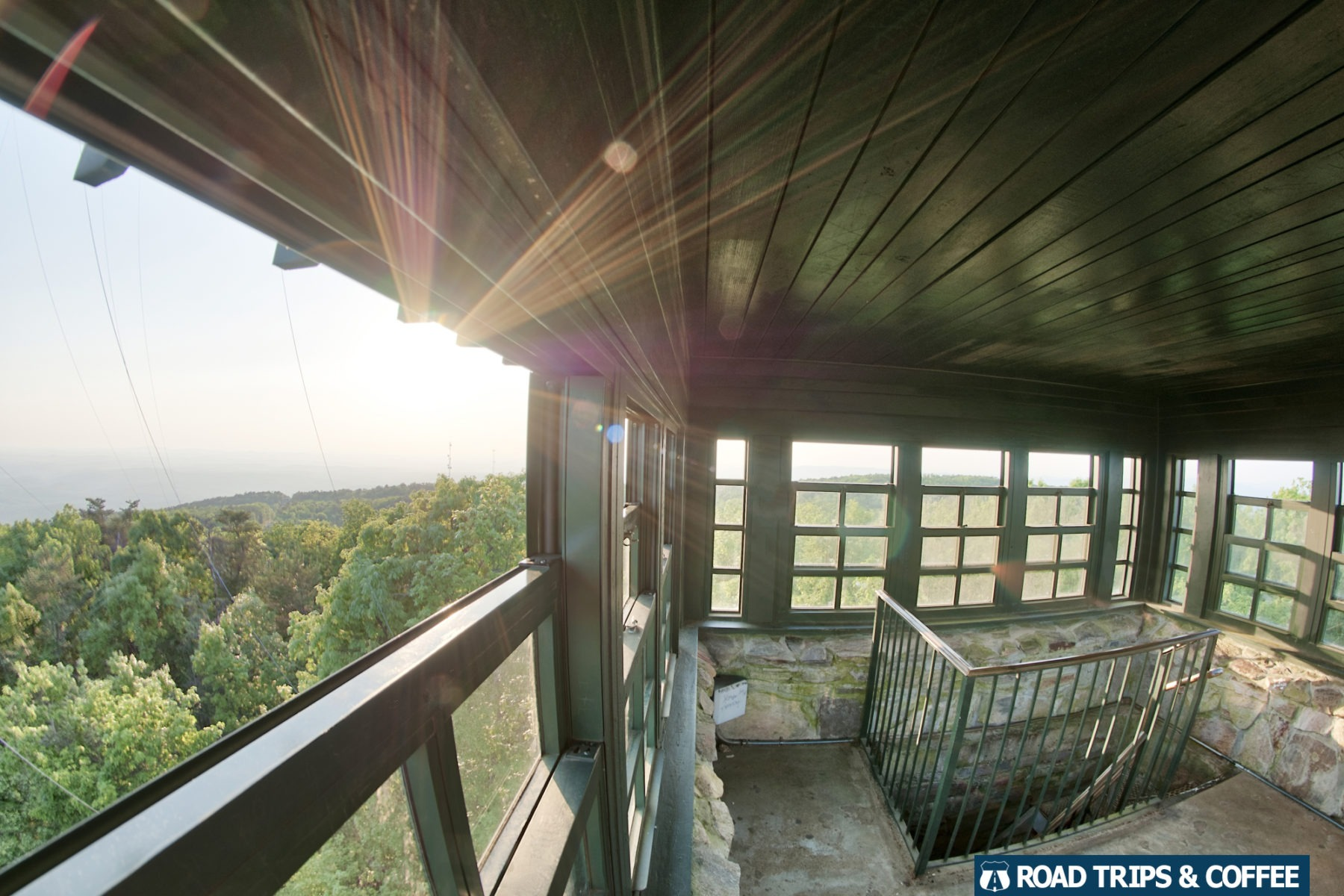 The setting sun flares through the large open windows of the Observation Tower at the top of Cheaha State Park in Alabama.