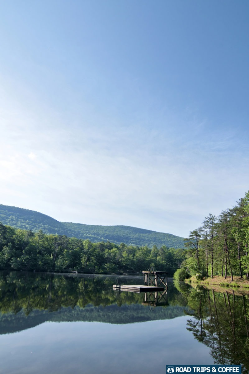 Perfectly calm water on a large lake reflecting the surrounding mountain and trees at Cheaha State Park in Alabama.