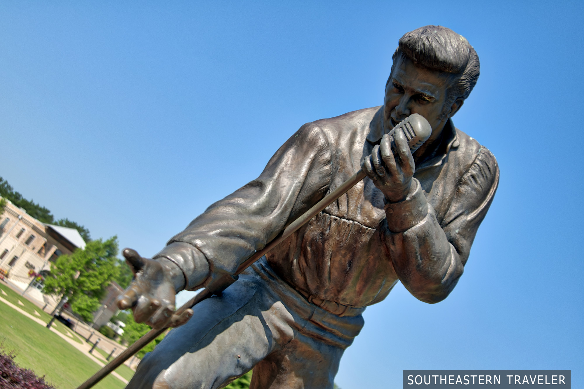 Larger than life statue of Elvis Presley singing in a concert in a park in Tupelo, Mississippi