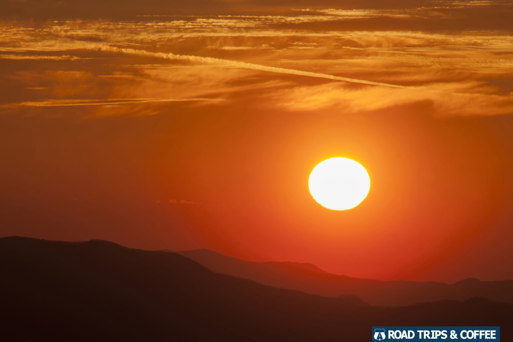 Warm orange colors cover the sky as the sun sets behind silhouetted mountains at the Cowee Mountain Overlook on the Blue Ridge Parkway in North Carolina