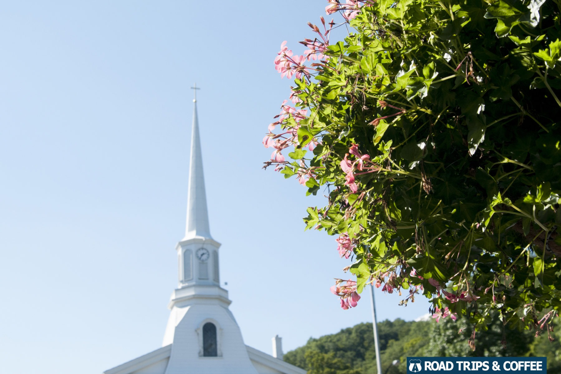 Beautiful blooming flowers and a towering church steeple in downtown Hammondsport, New York