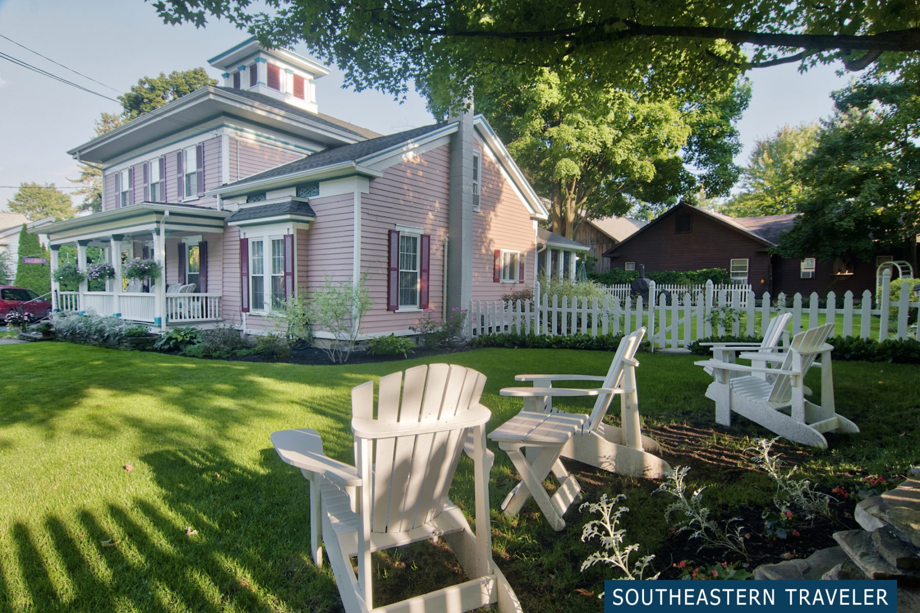 Outside the Blushing Rose Bed and Breakfast with adirondack chairs on a beautiful lawn beneath the shade of a tree