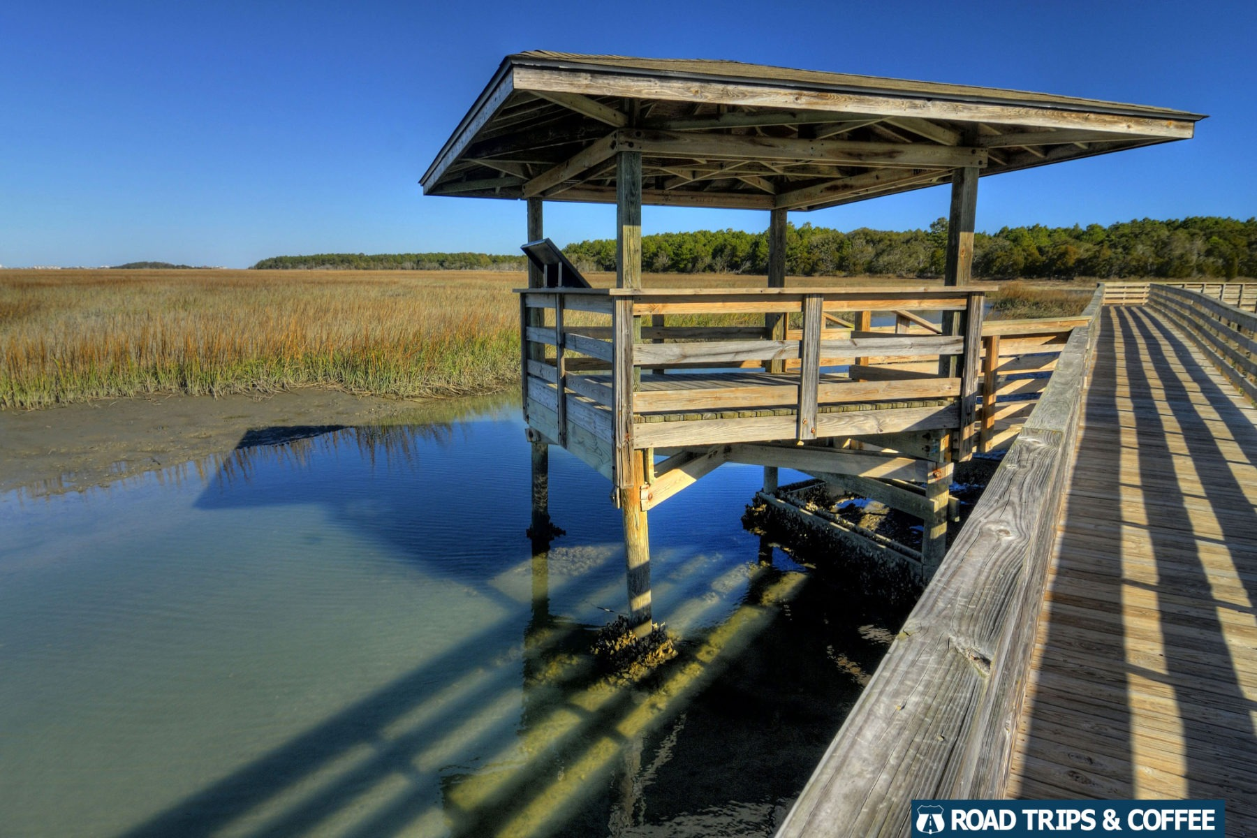A covered shelter along a wooden boardwalk over the water at Huntington Beach State Park in Murrells Inlet, South Carolina
