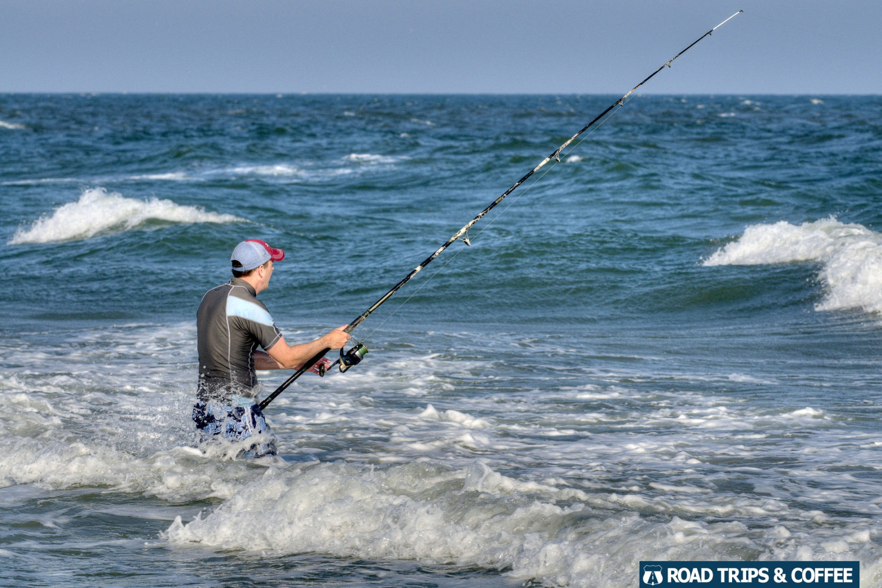 A man with a long fishing rod stands waist deep in the ocean on a beach at Huntington Beach State Park in Murrells Inlet, South Carolina