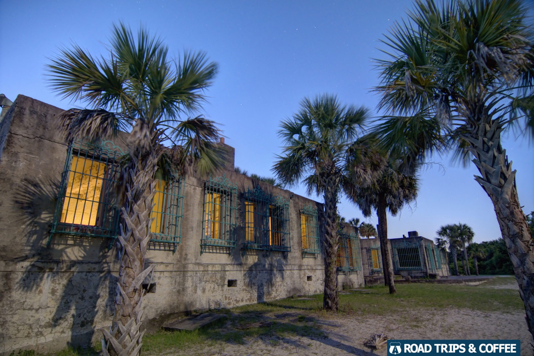 Dusk with dark blue skies and lights from inside Atalaya Castle at Huntington Beach State Park in Murrells Inlet, South Carolina