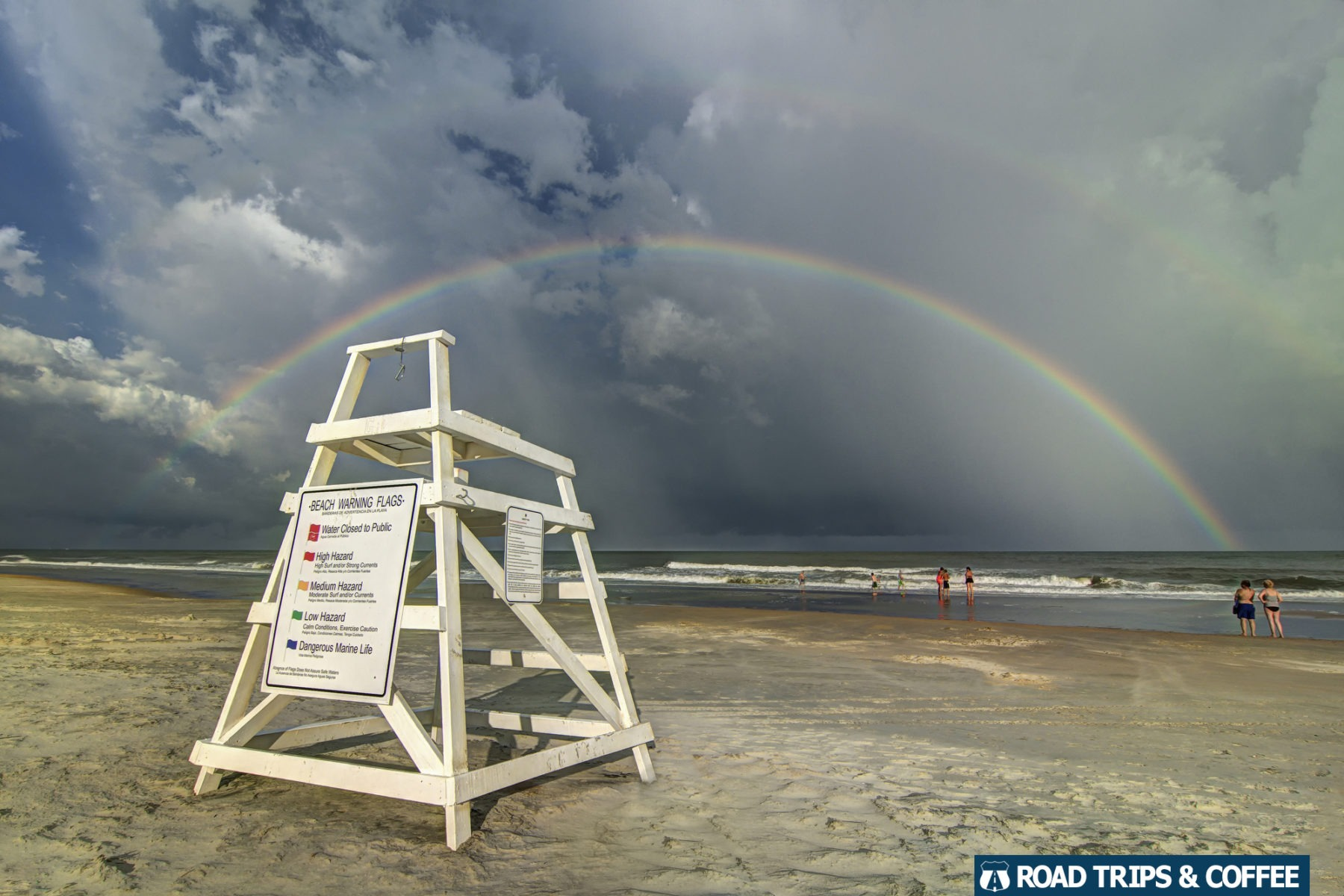 A rainbow stretches across the ocean in front of a dark thunderstorm with a bright white lifeguard chair beneath at Huntington Beach State Park in Murrells Inlet, South Carolina