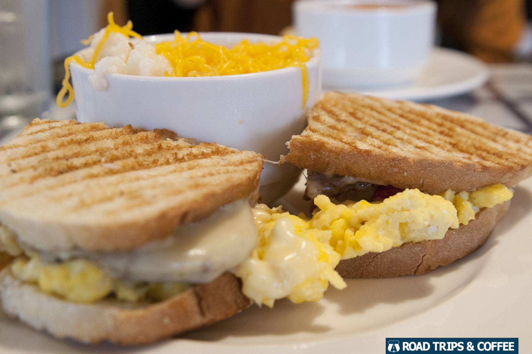 A bowl of cheese grits and two halves of a breakfast sandwich at The Gourmet Shop during brunch in Columbia, SC