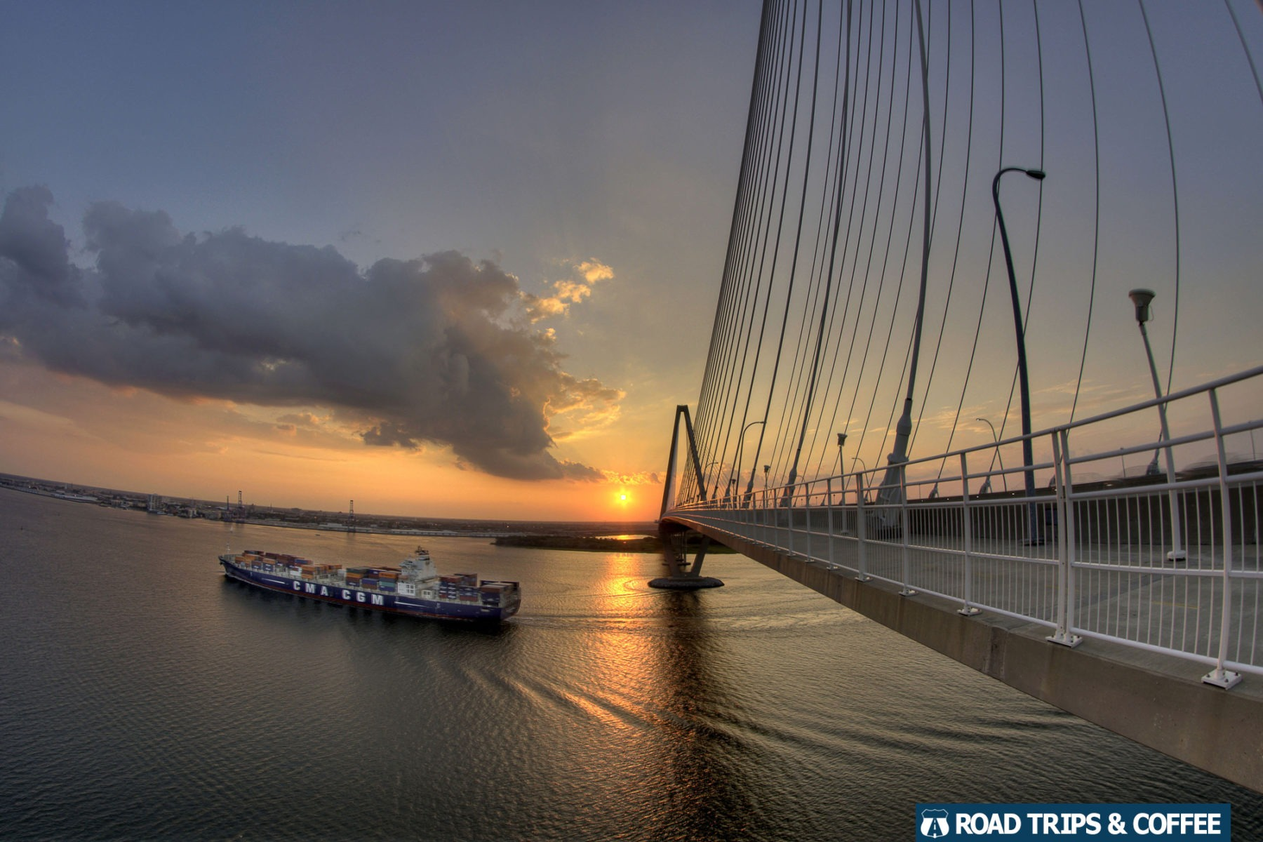 A large cargo ship cruises on the river during sunset beneath the long Arthur Ravenel Junior Bridge in Charleston, South Carolina
