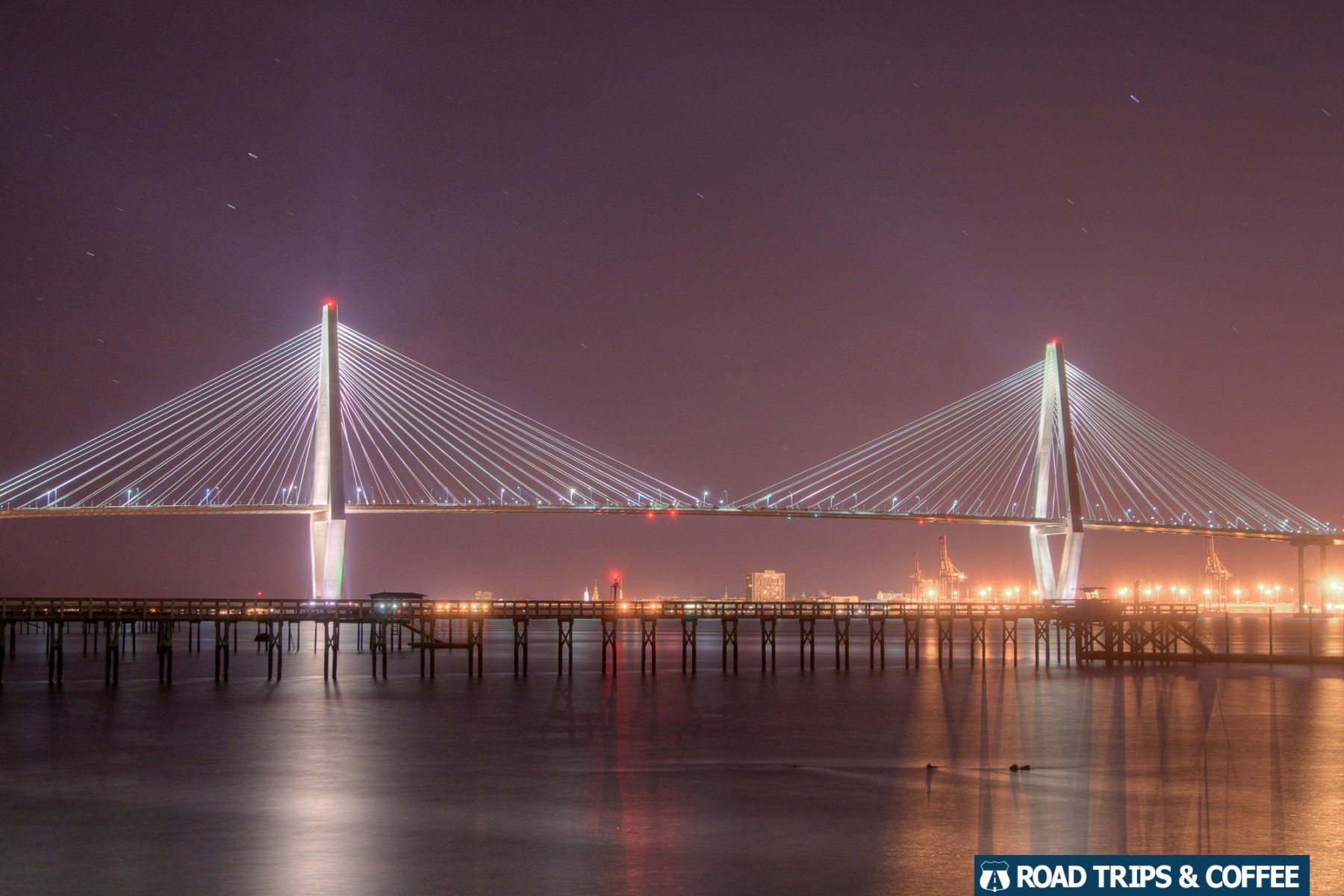 The Arthur Ravenel Junior Bridge lights up the night sky across the harbor in Charleston, South Carolina