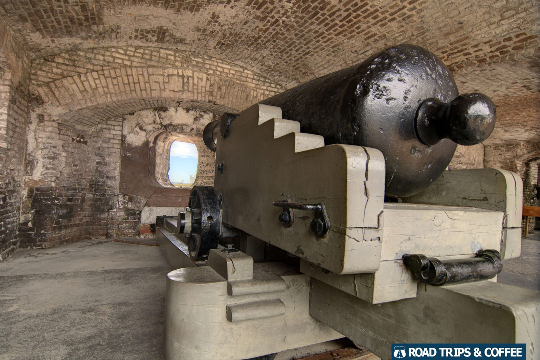 A massive cannon points through a small opening overlooking the harbor at Fort Sumter and Fort Moultrie National Historic Site in Charleston, South Carolina