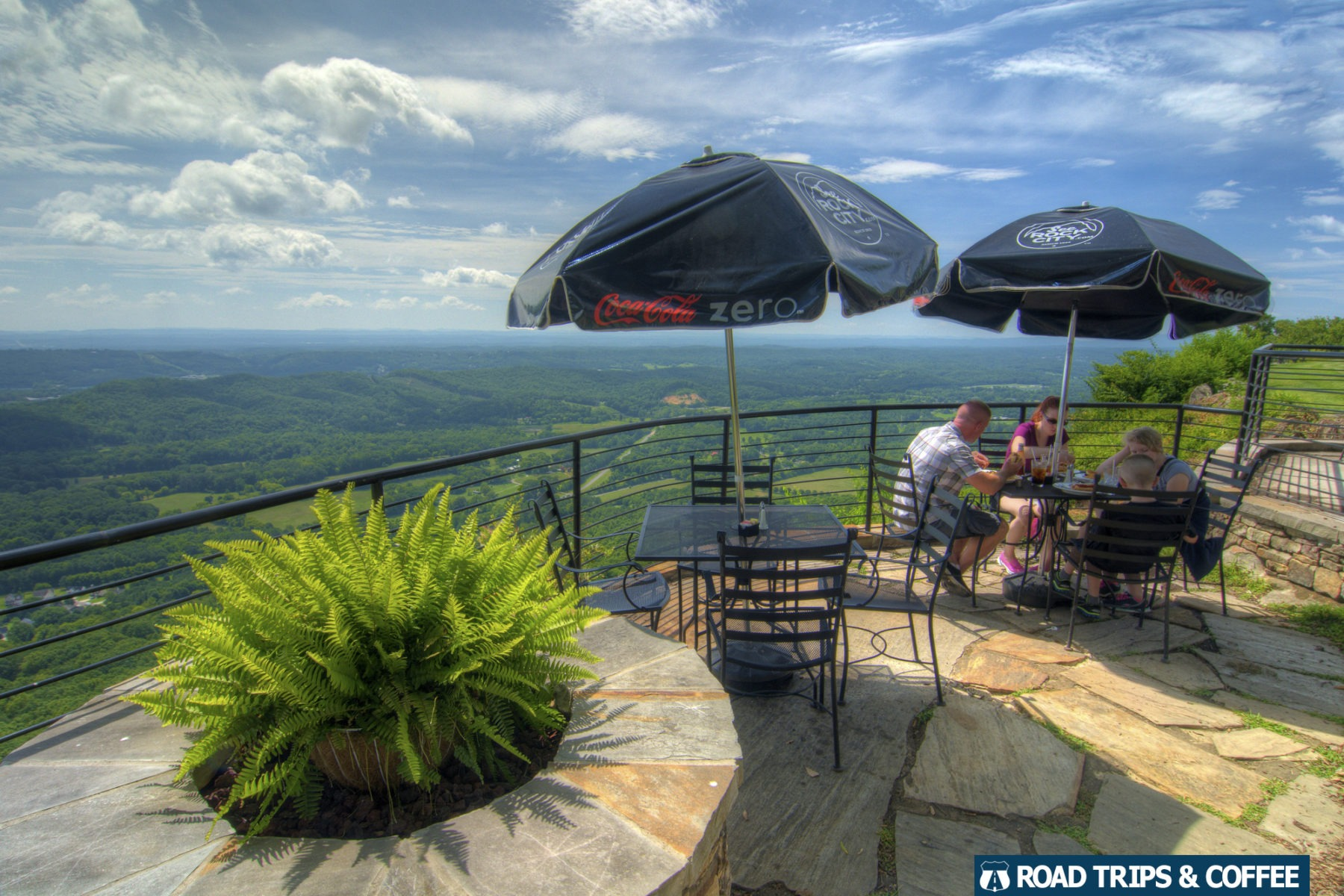 A couple of tables on a stone patio with a stunning view of the local landscape at Rock City in Lookout Mountain, Tennessee