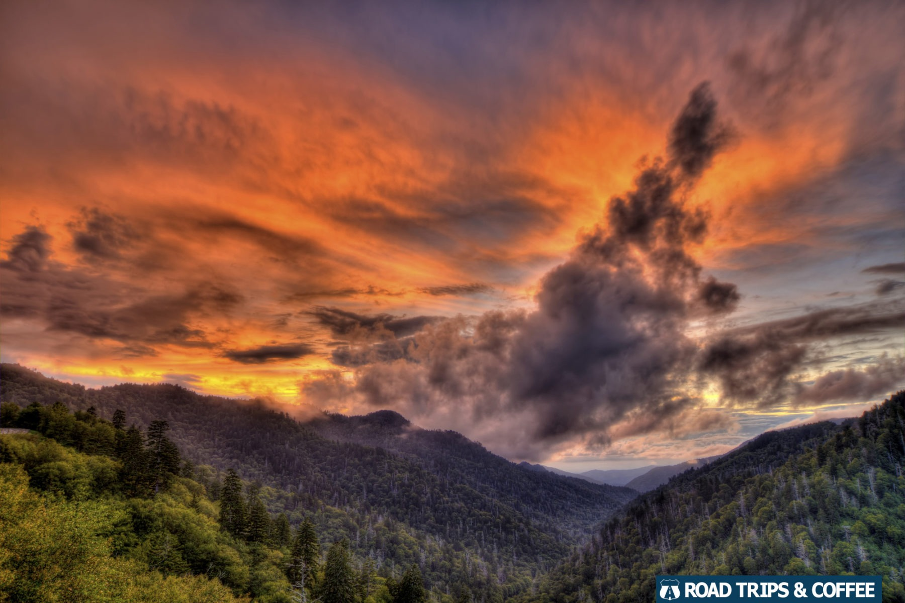 A warm orange sunset spreads across the sky above the mountain landscape at the Morton Overlook in the Great Smoky Mountains National Park