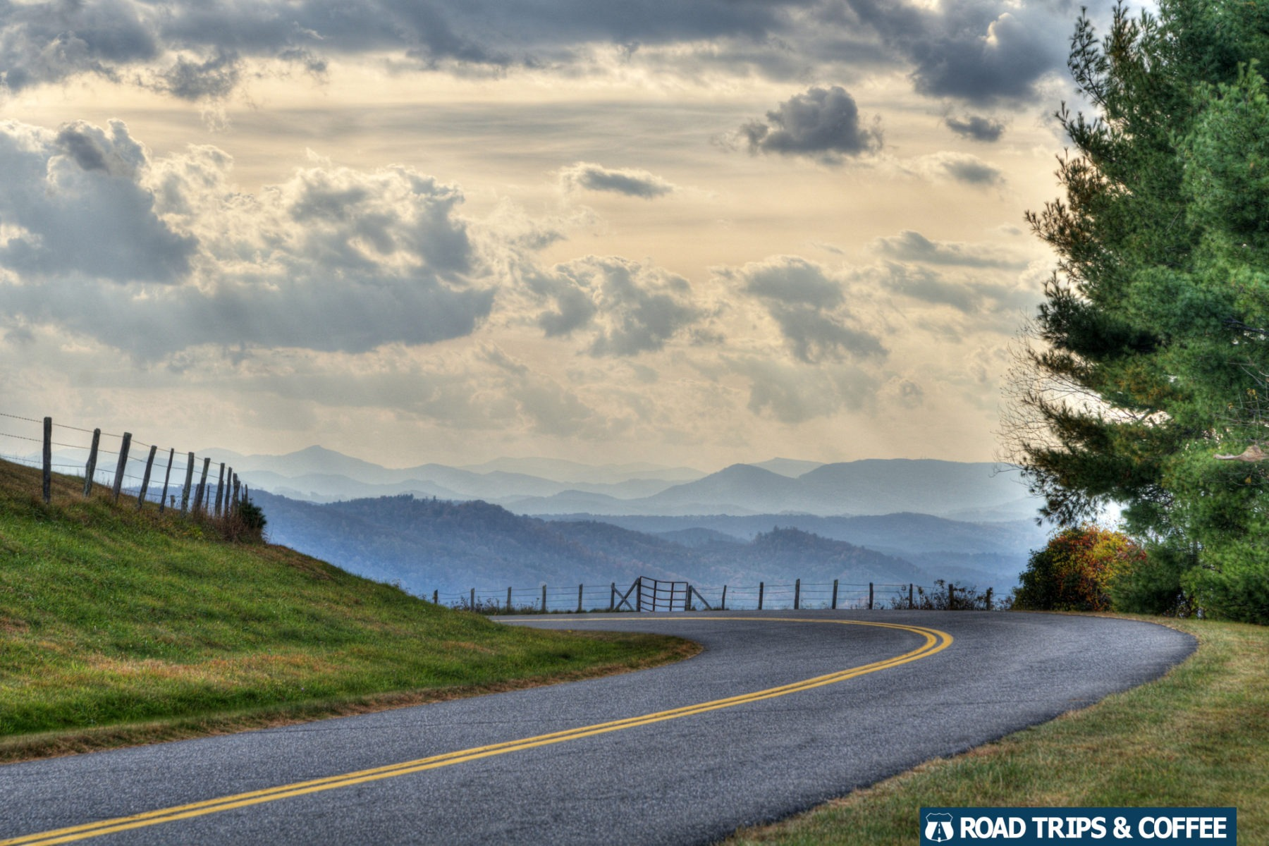 A slight curve on the Blue Ridge Parkway with a view of mountains in the distance in North Carolina.