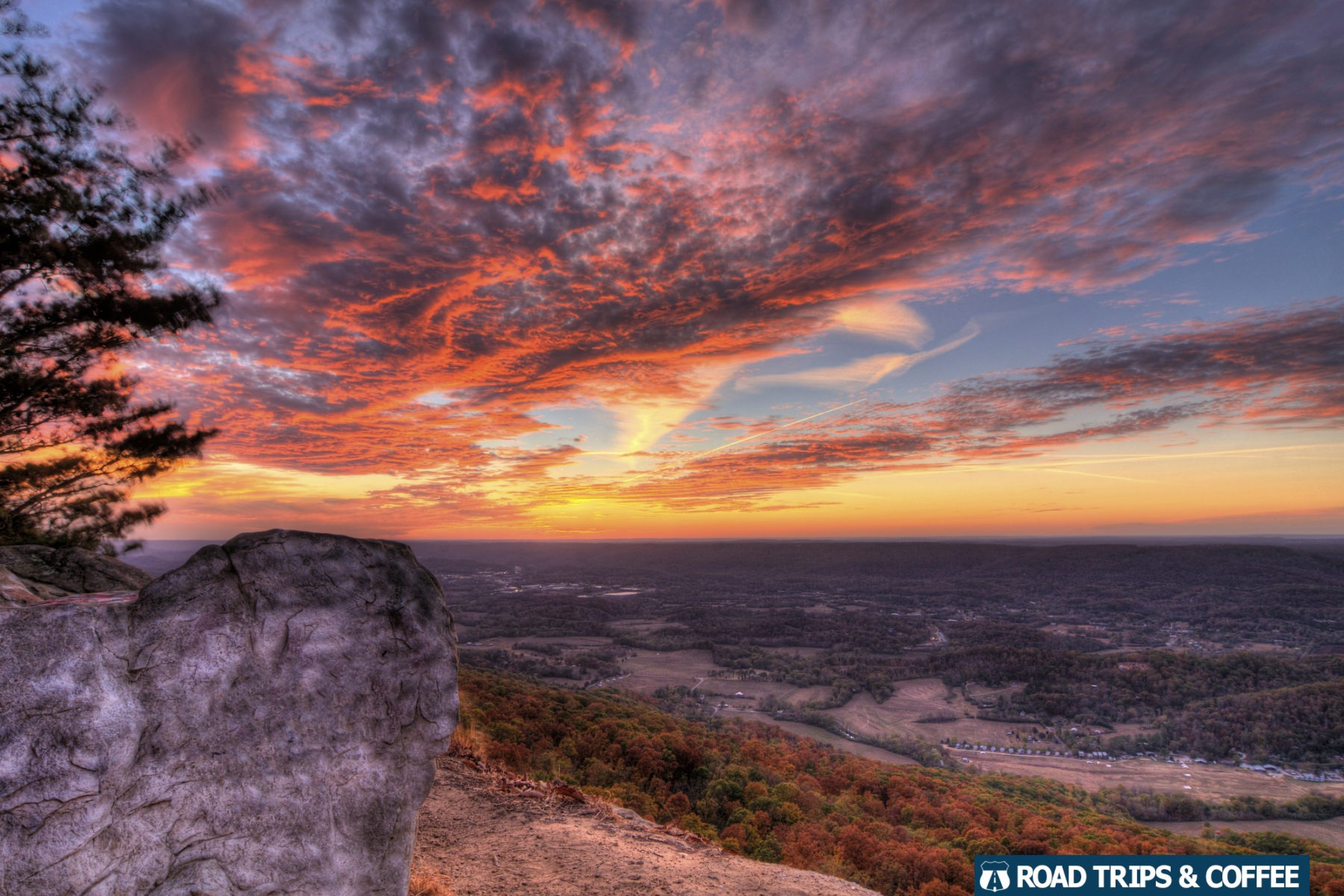 Warm oranges and pinks spread across the clouds during sunset in Lookout Mountain, Georgia