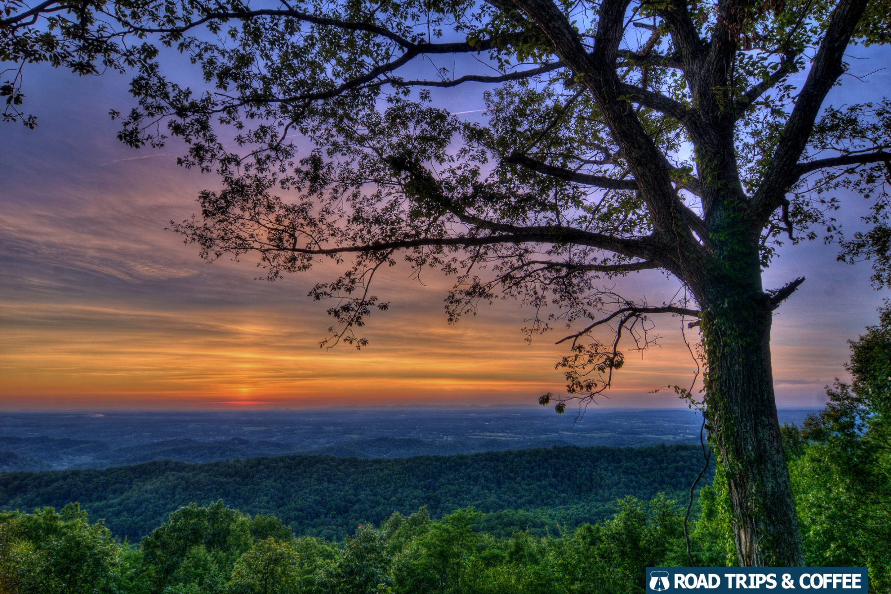A warm sunset across the low-lying landscape beyond the Foothills Parkway in the Great Smoky Mountains National Park