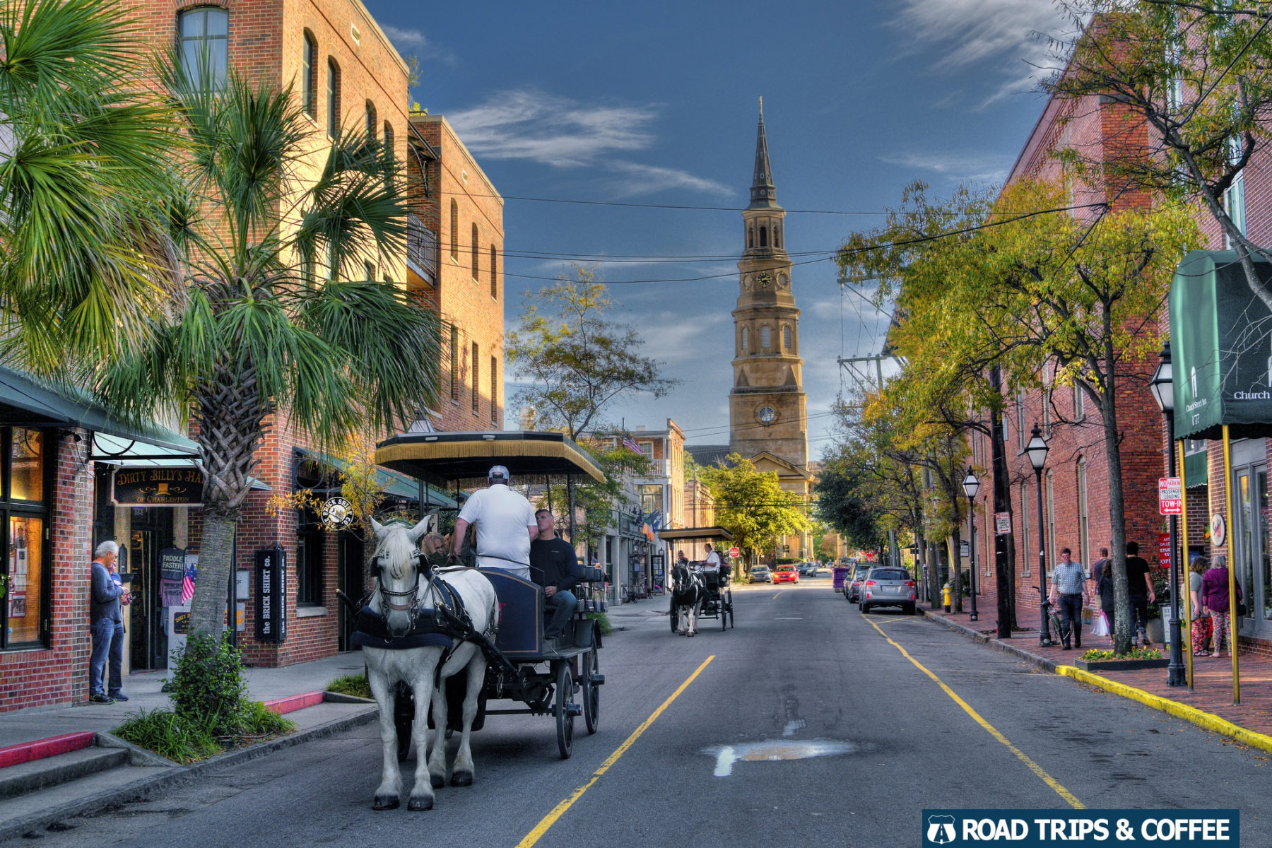 Two horse drawn carriages travel down an empty street with the steeple of Saint Phillips Episcopal Church in the background in Charleston, South Carolina