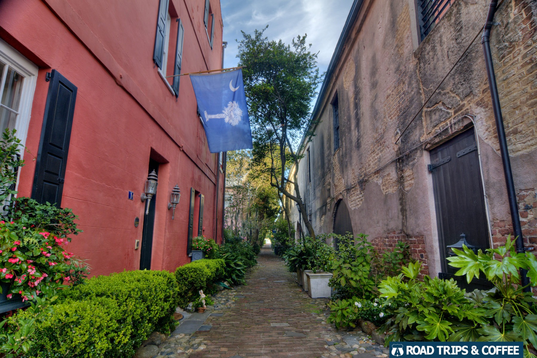 A vibrant pink wall of a brick alley in downtown Charleston, South Carolina