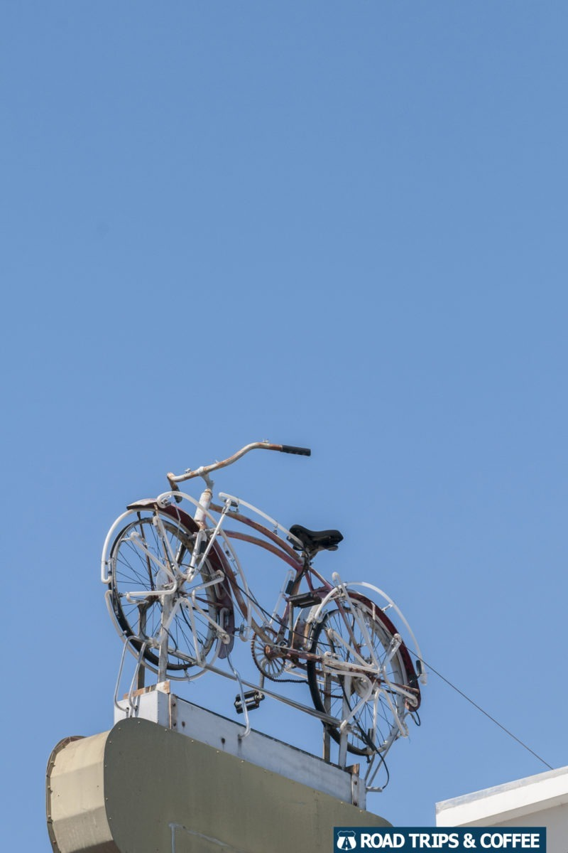 An old bicycle hanging above a sign on a building in Charleston, South Carolina
