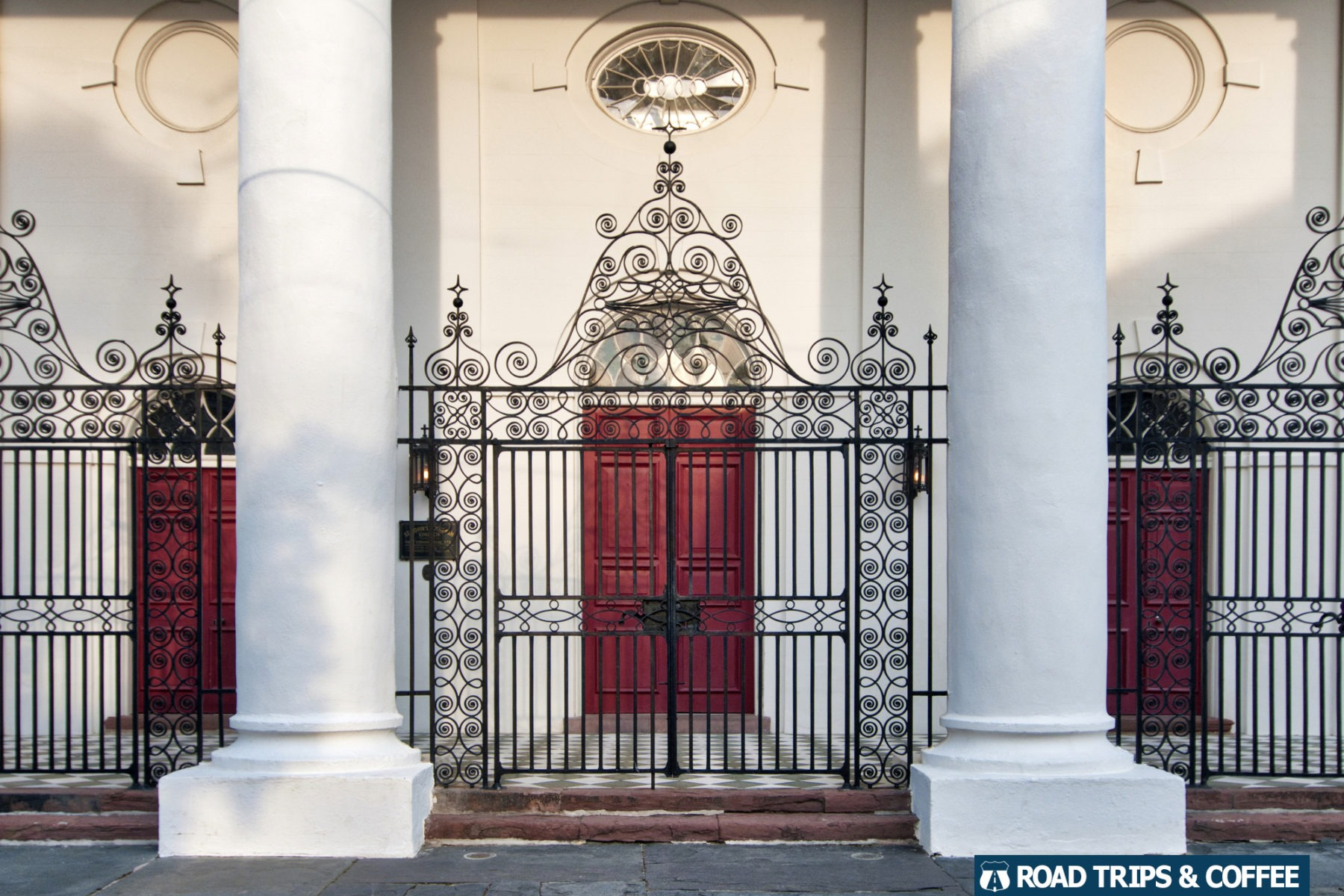 Vibrant red doors behind a wrought iron fence at St. John's Lutheran Church in Charleston, South Carolina