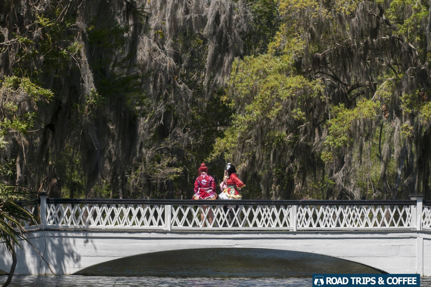 Two women dressed as 1800s women walk across a bridge at Magnolia Plantation and Garden in Charleston, South Carolina