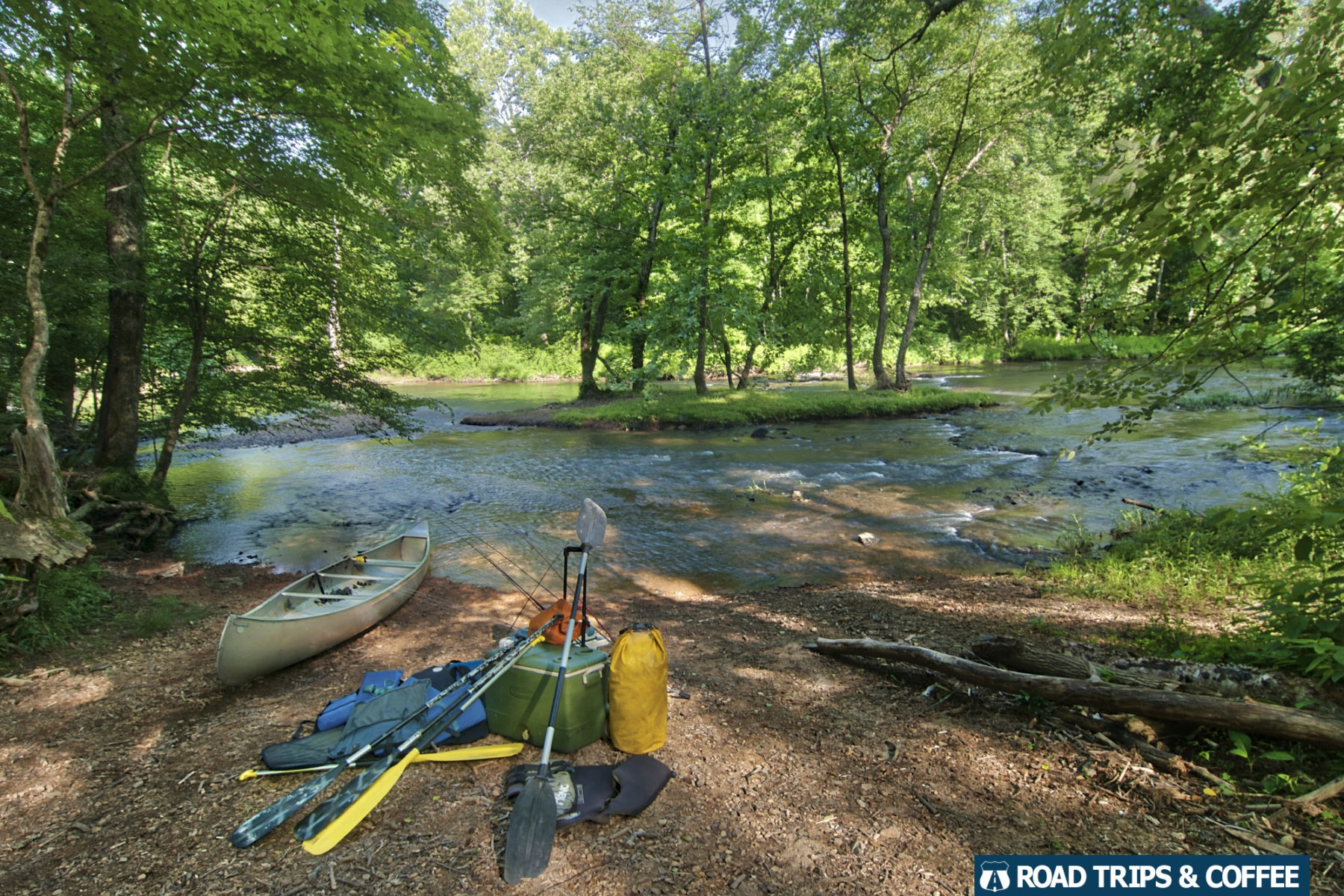 A canoe with paddles, fishing rods, and a cooler ready to get into the river at Metal Ford on the Natchez Trace Parkway in Tennessee
