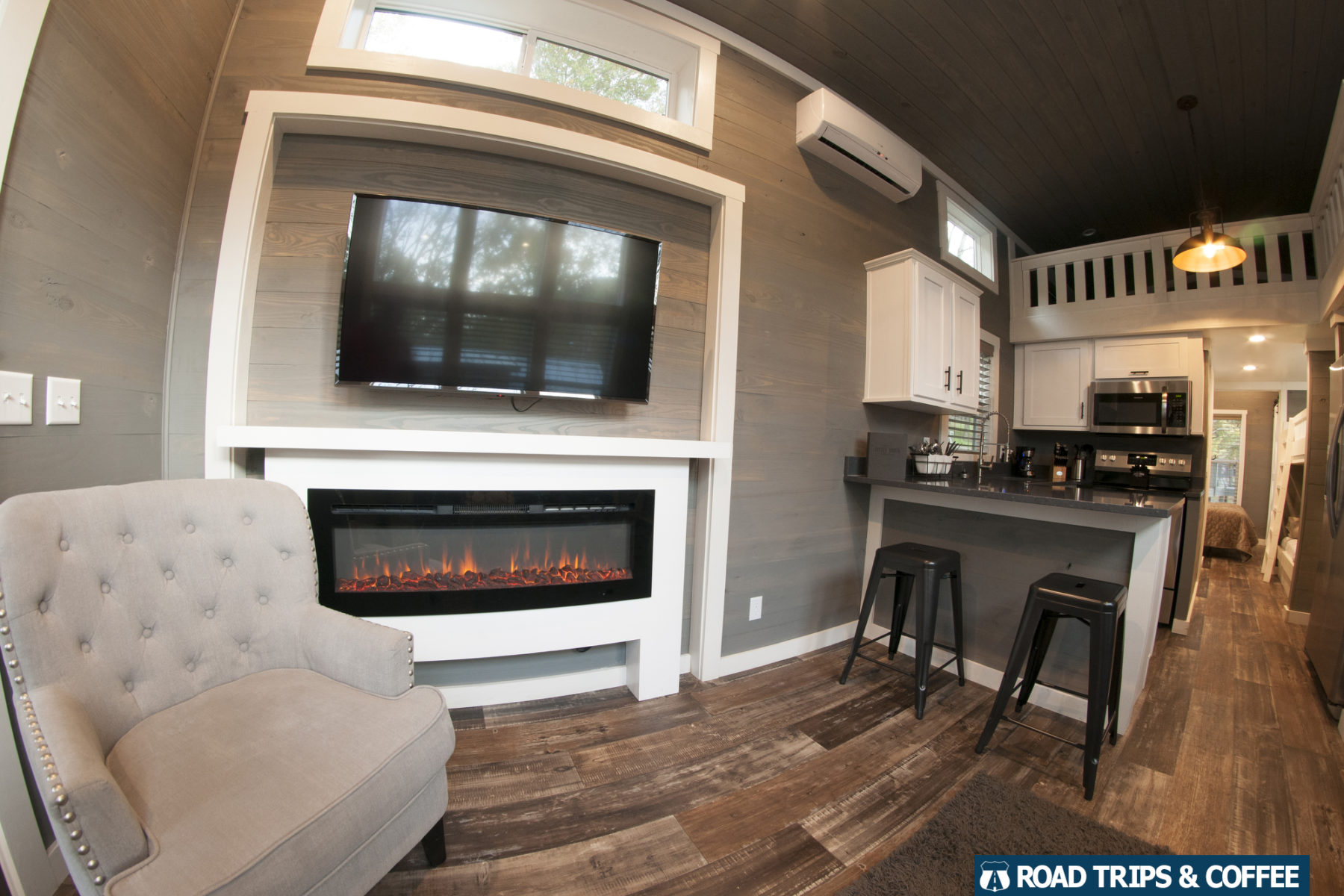 An armchair beside an electric fireplace and television in a tiny home at Little Arrow Outdoor Resort in Townsend, Tennessee