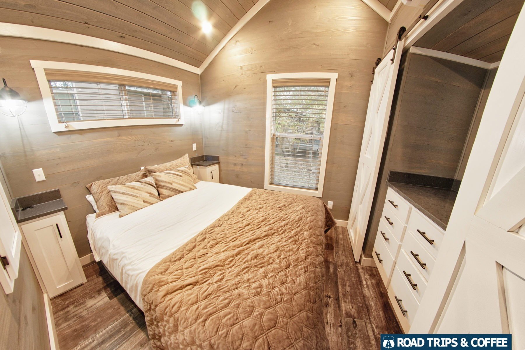 A queen bed with a built-in closet and nightstands in a tiny home at Little Arrow Outdoor Resort in Townsend, Tennessee