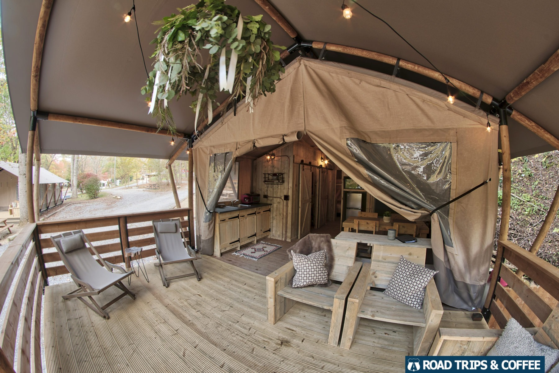 Covered front deck with wooden furniture at a glamping tent at Little Arrow Outdoor Resort in Townsend, Tennessee
