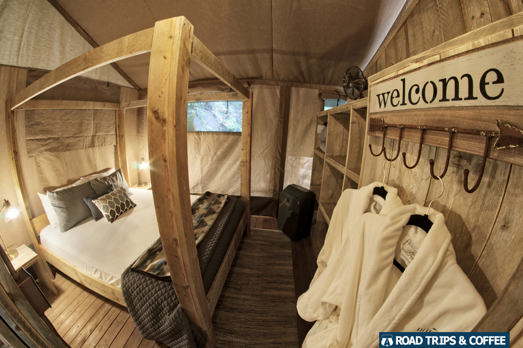 A small master bedroom with comfortable robes hanging from hooks inside a glamping tent at Little Arrow Outdoor Resort in Townsend, Tennessee