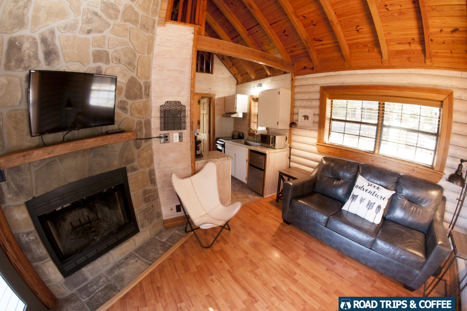 A fireplace, television, and comfortable leather couch inside a premiere cabin at Little Arrow Outdoor Resort in Townsend, Tennessee