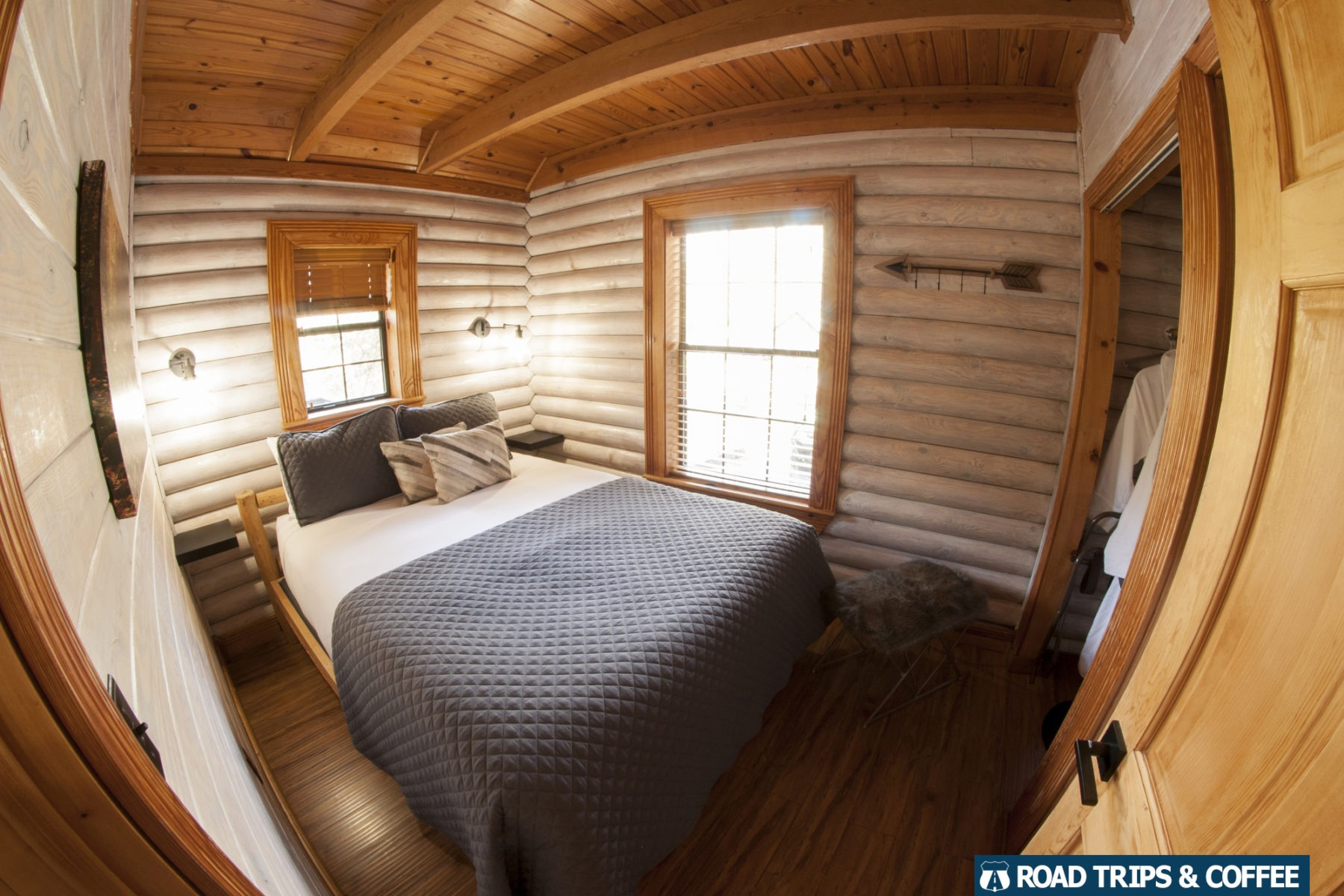A queen bed inside the white-washed premiere cabin at Little Arrow Outdoor Resort in Townsend, Tennessee