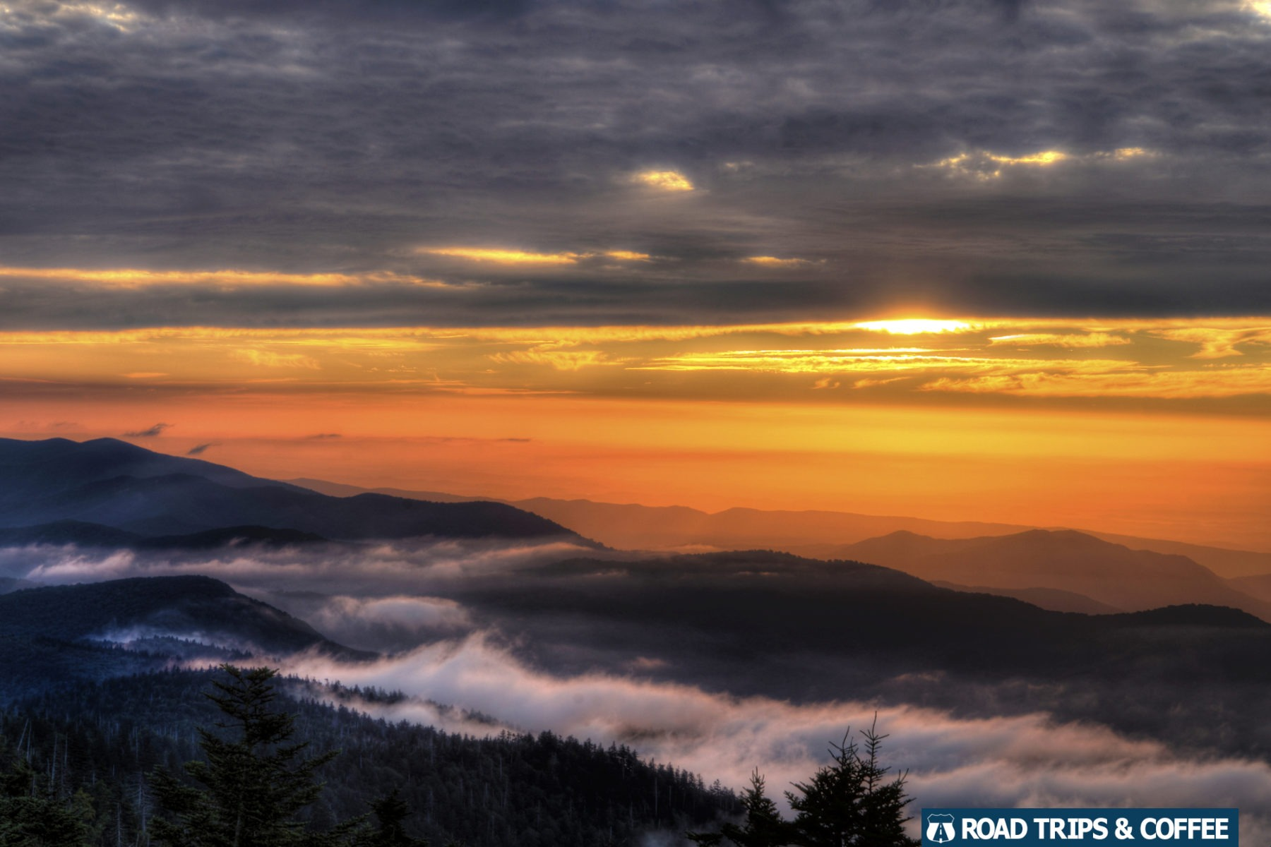 A warm orange sunset above lingering clouds on the mountains at Clingman's Dome in the Great Smoky Mountains National Park
