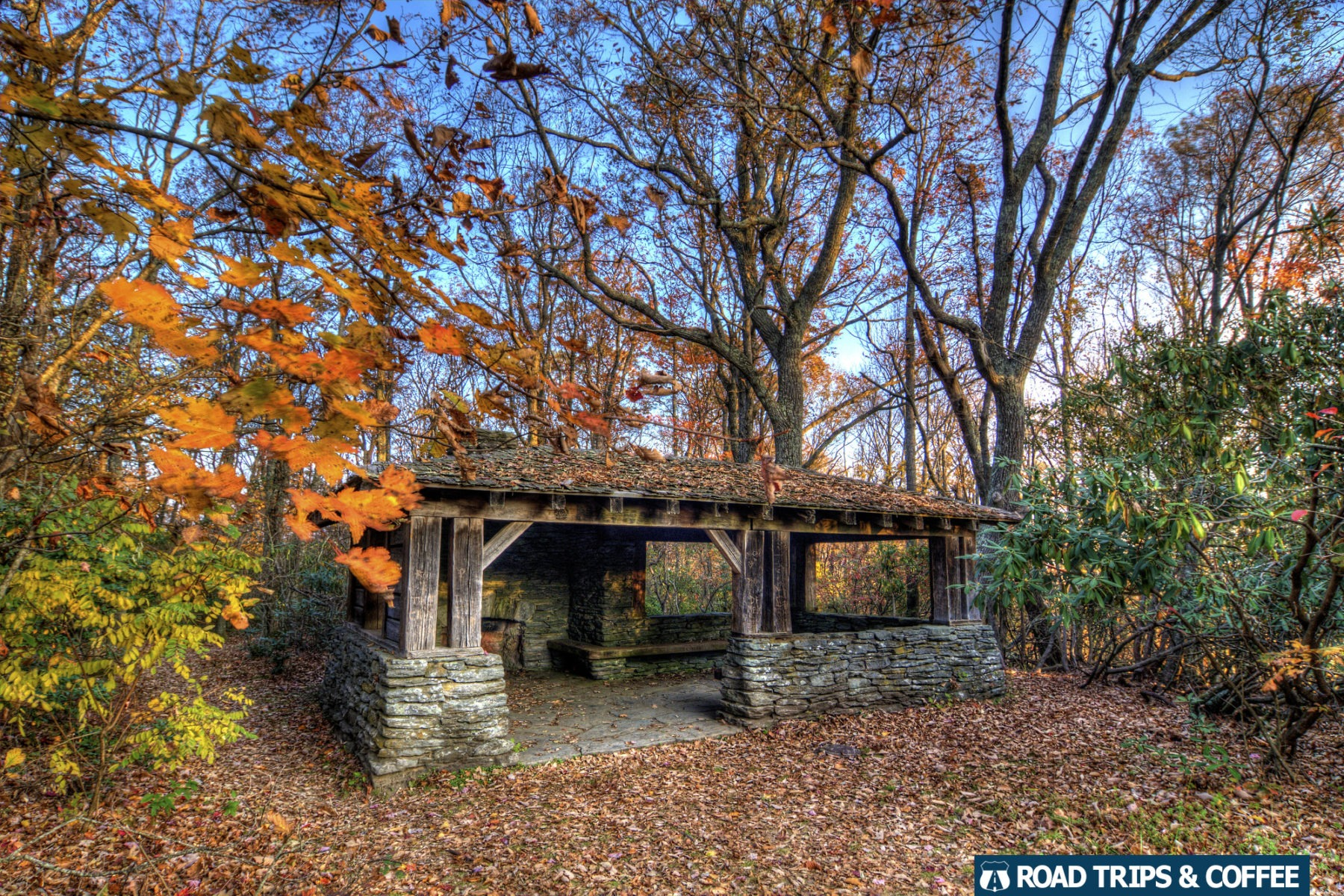 A rustic covered shelter surrounded by trees and fall colors at Cumberland Knob Recreation Area on the Blue Ridge Parkway in North Carolina