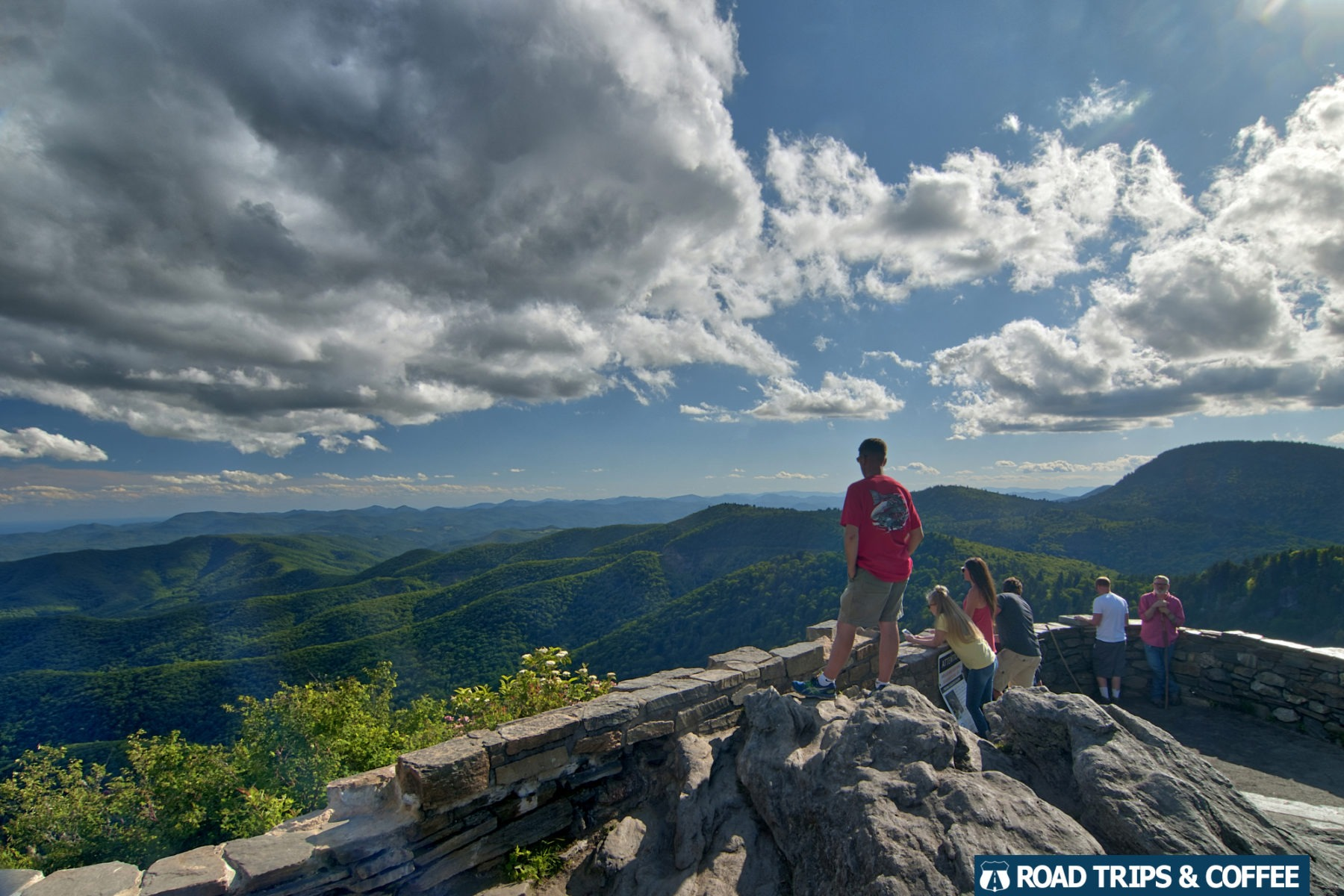 A family enjoys the view from the Devil's Courthouse Overlook on the Blue Ridge Parkway in North Carolina
