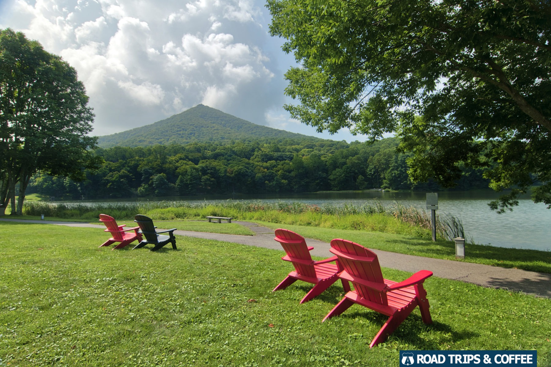 View of Sharp Top Mountain across Abbott Lake with a set of adirondack chairs on the lawn at the Peaks of Otter on the Blue Ridge Parkway in Virginia