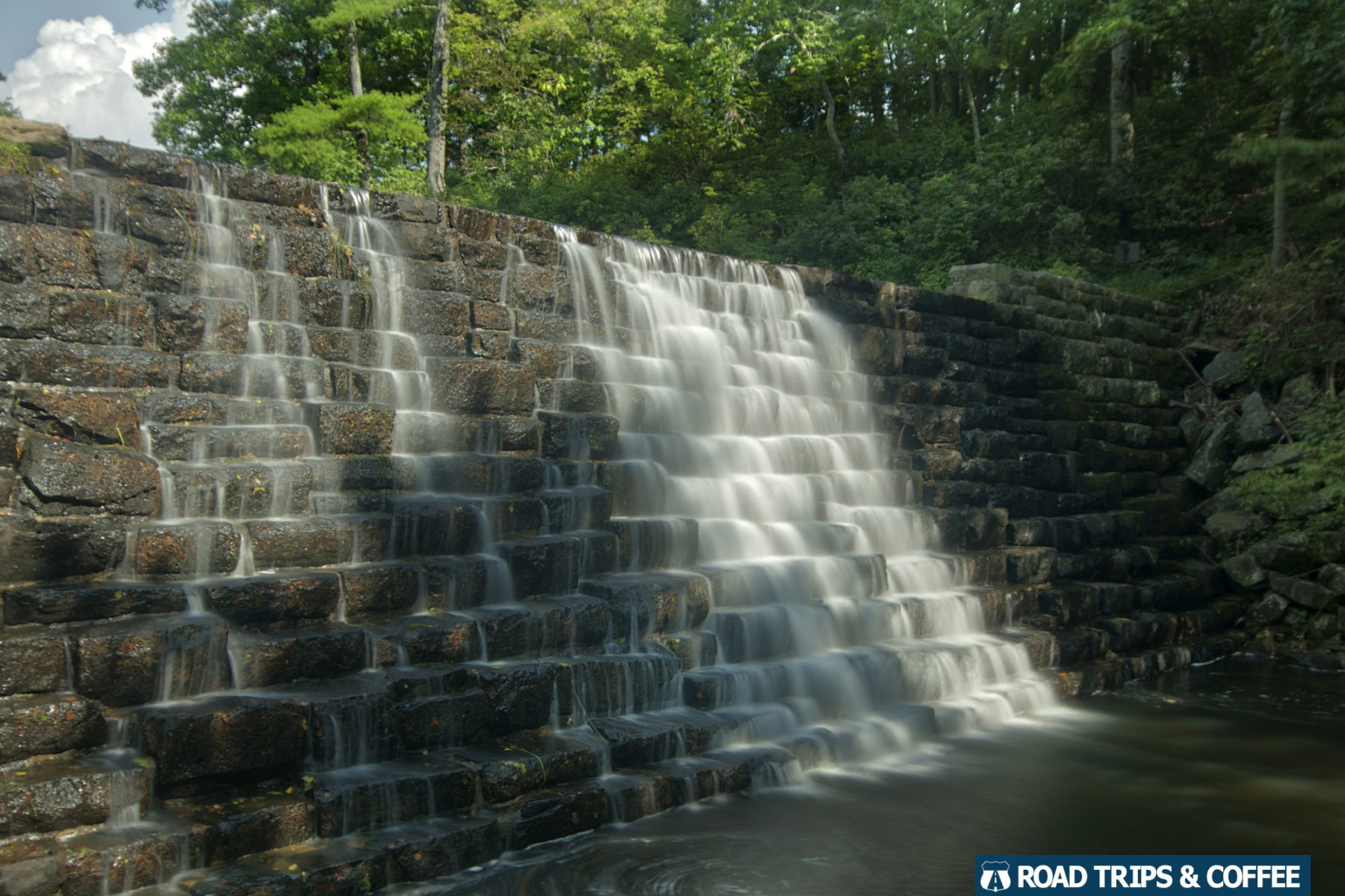 A waterfall spilling over the stone dam at Otter Lake on the Blue Ridge Parkway in Virginia