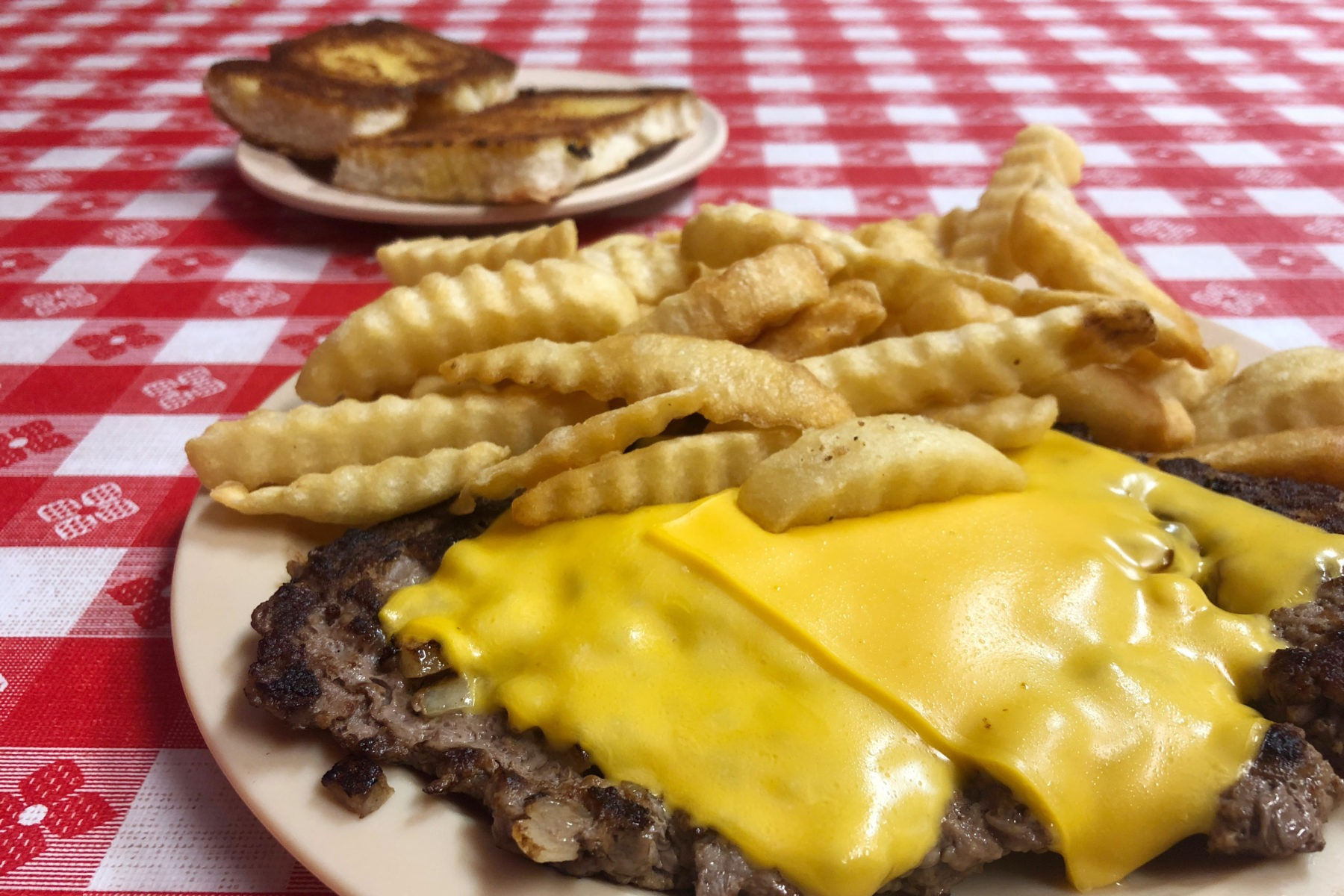 The cheesburger steak meal with a large grilled hamburger patty topped with melted cheese and surrounded with crinkle cut french fries from Johnny's Big Burger in Clarksville, Tennessee