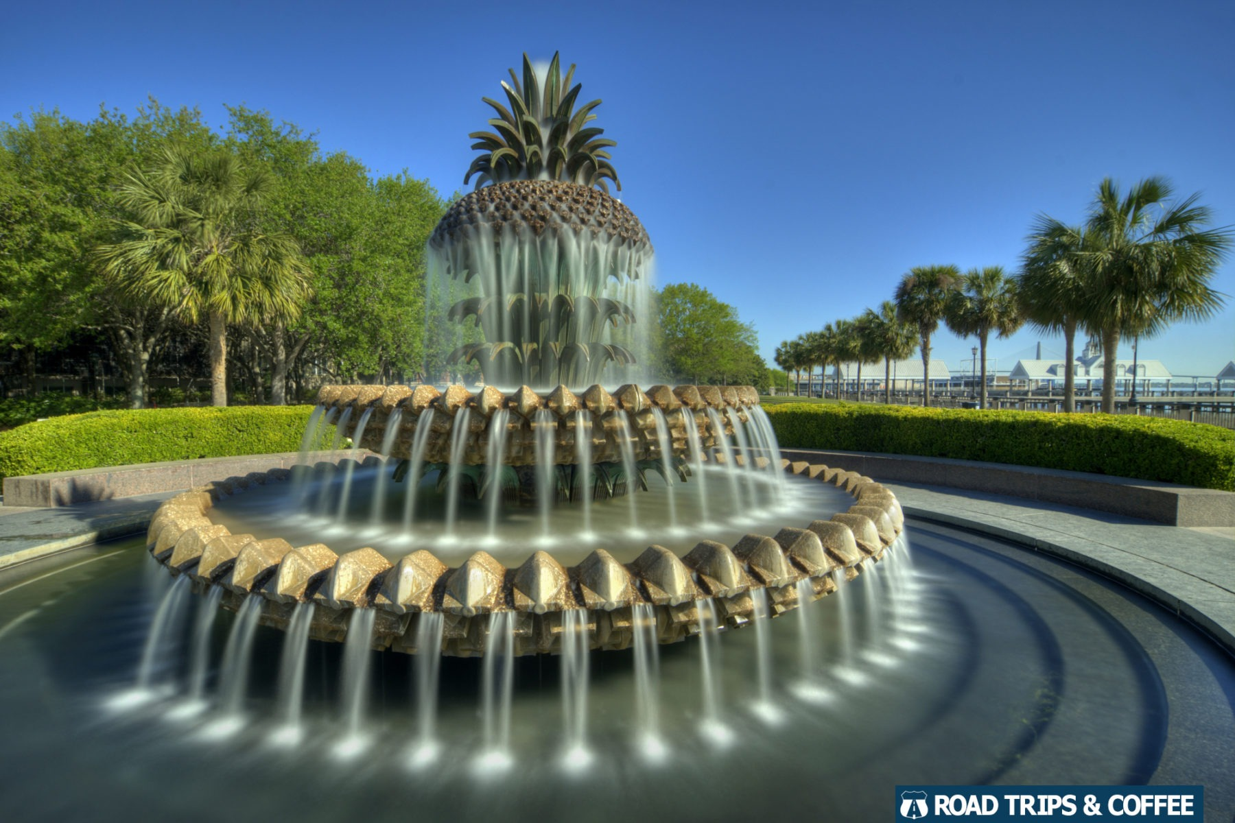 Water spills out of a concrete foundtain shaped like a pineapple at Waterfront Park in Charleston, South Carolina