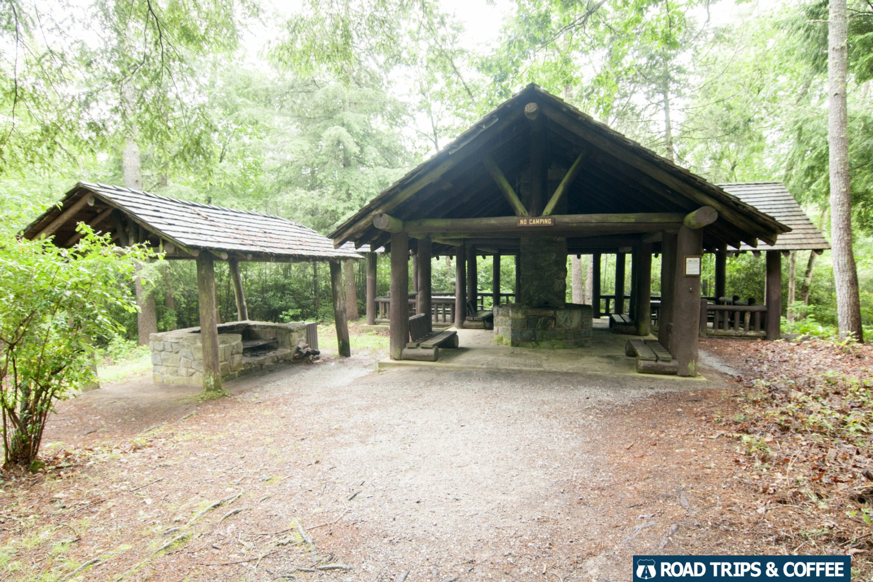Large covered shelters surrounded by a dense forest on a rainy day at Cliffside Lake Recreation Area in Highlands, North Carolina