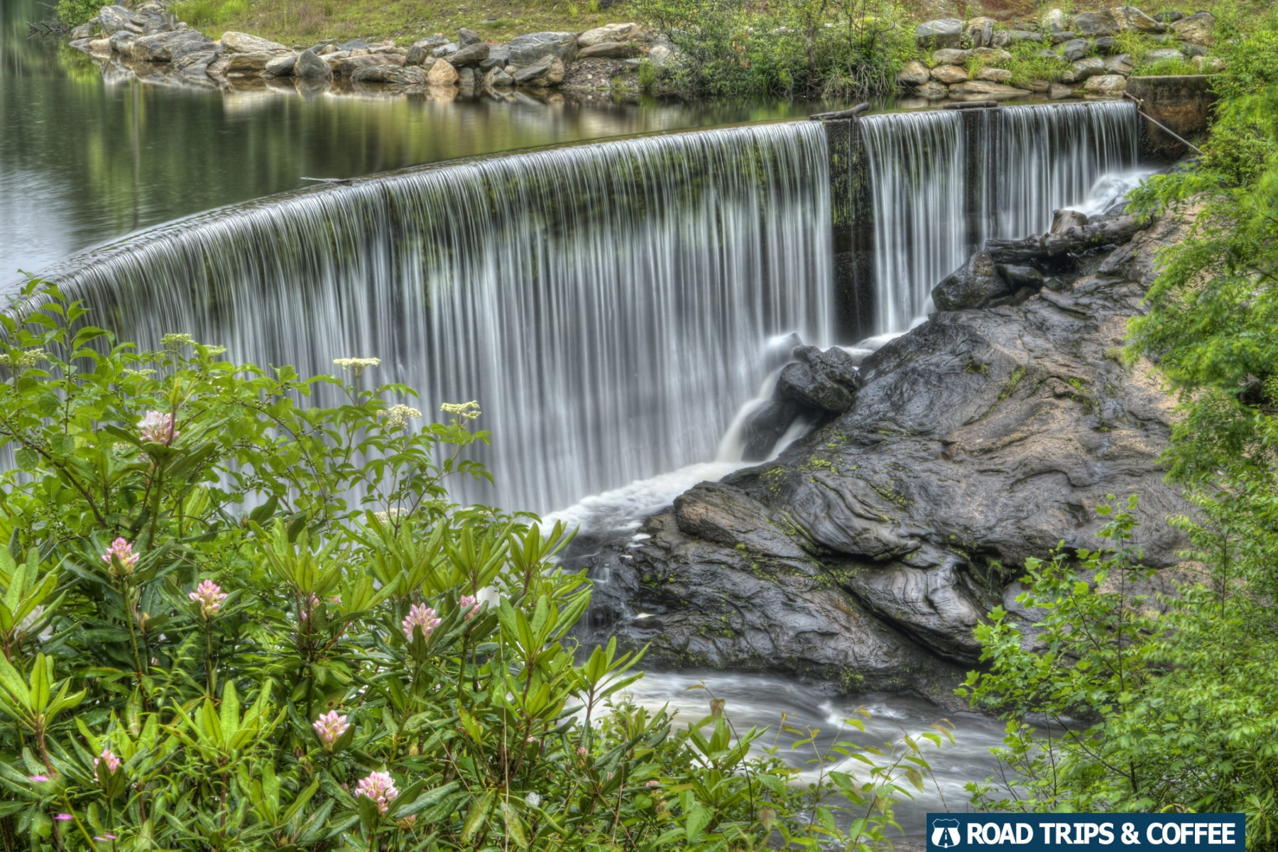 Water spills over the top of a small stone dam at Sequoyah Falls in Highlands, North Carolina