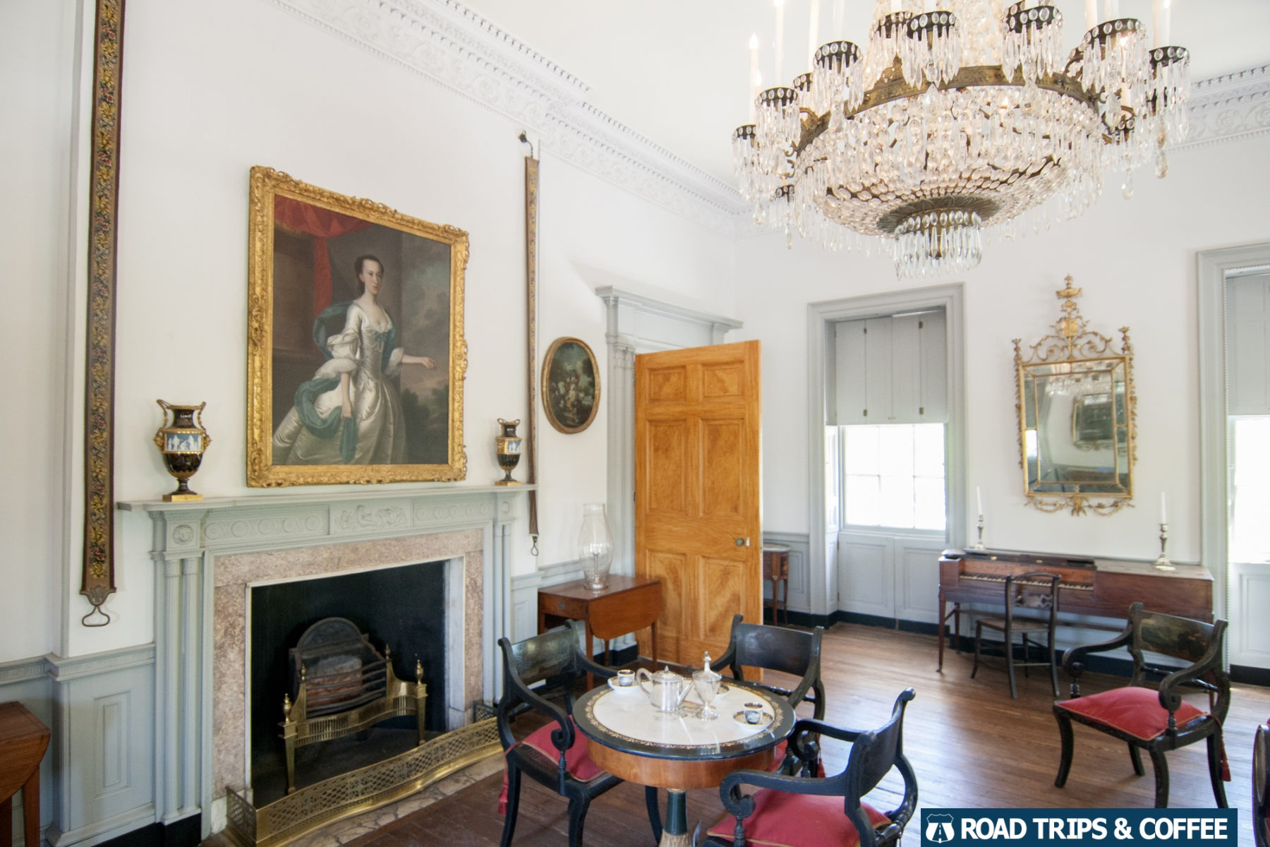 Posh decorated historic room with a hanging chandelier and portrait paintings on the walls at the Joseph Manigault House in Charleston, South Carolina